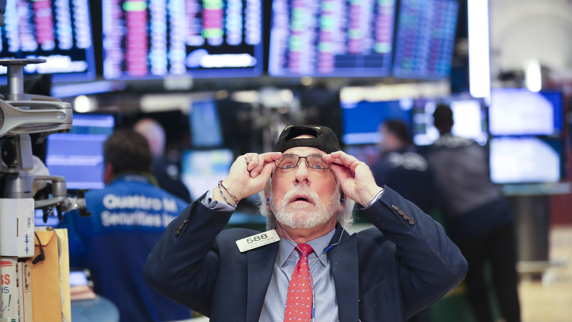 Stock market trader adjusts his glasses.