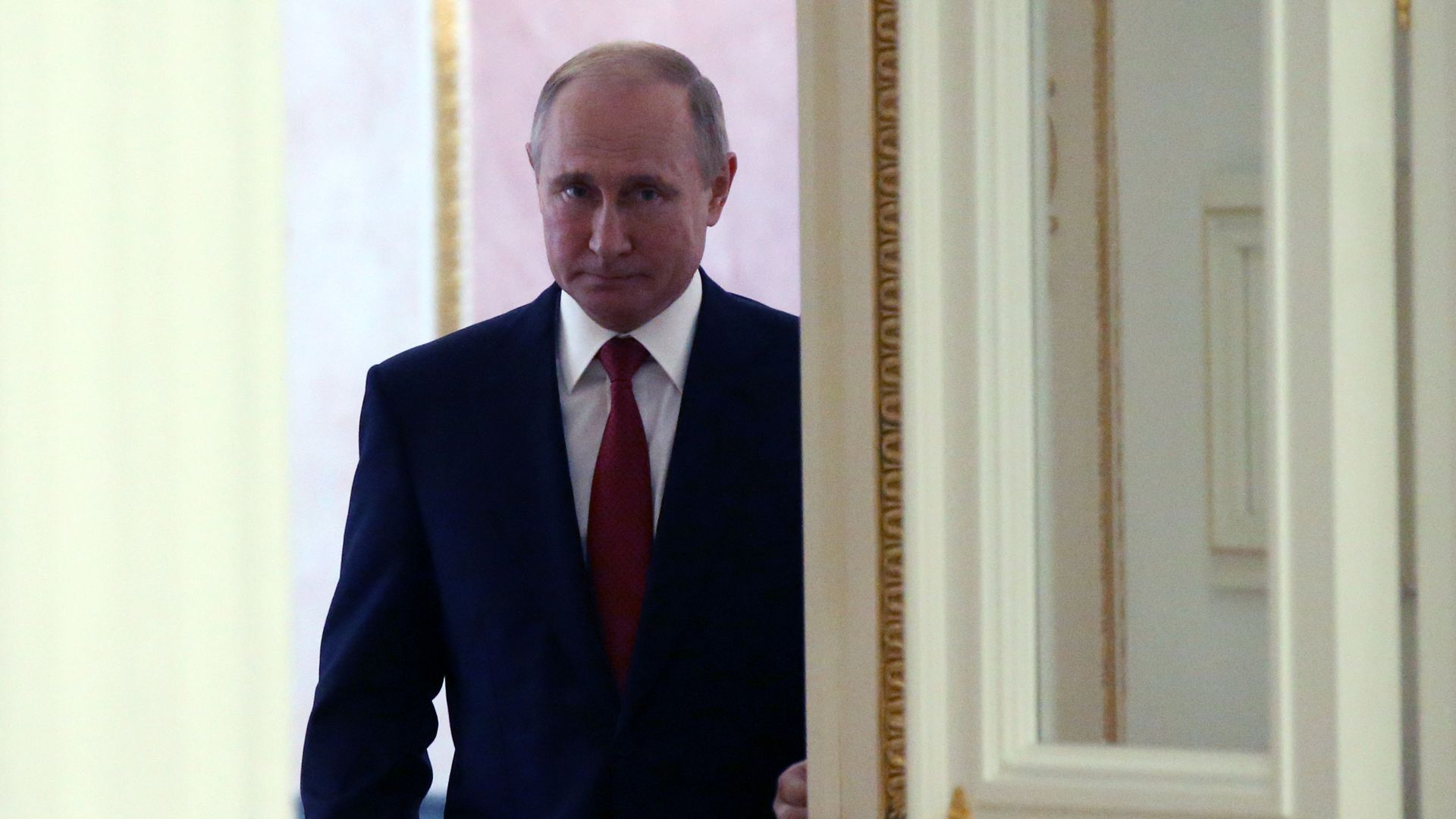 Vladimir Putin stands near a door and looks meek.