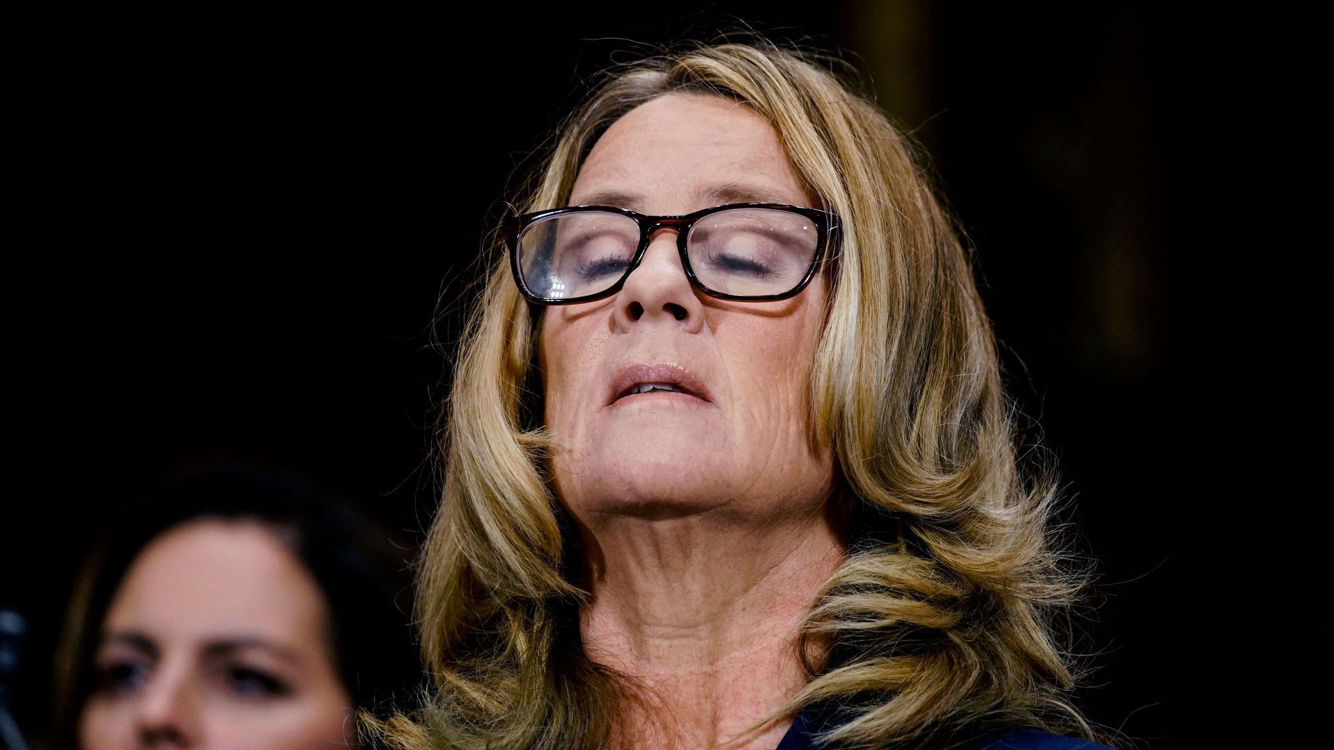 Dr. Christine Blasey Ford closes eyes and lifts head to sky.
