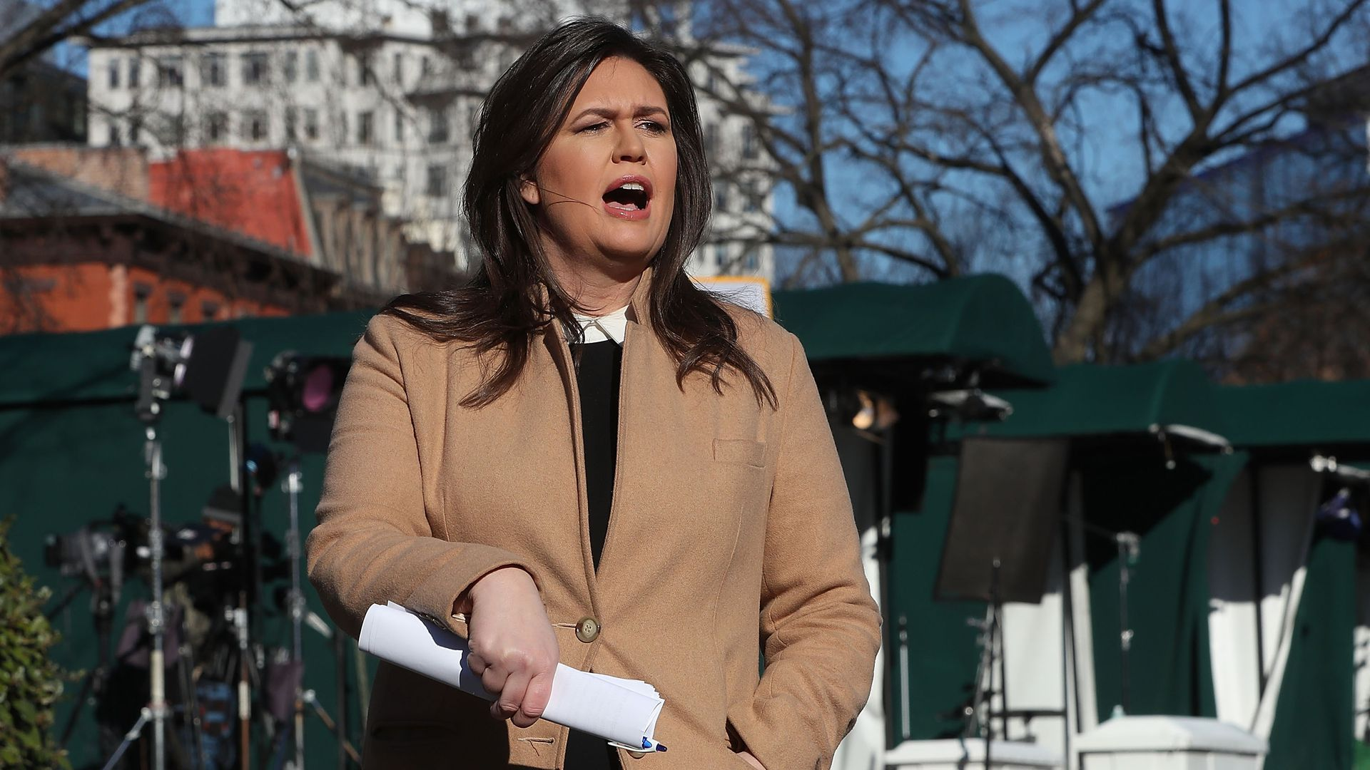 Sarah Sanders talking to reporters with a beige coat on.