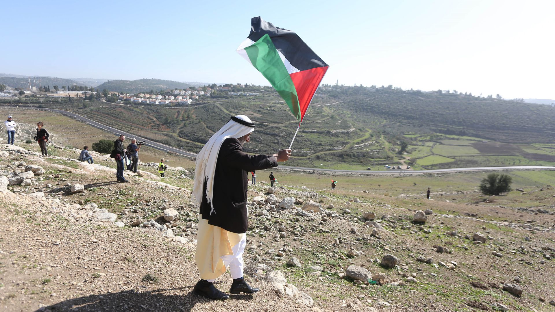 A Palestinian man waves Palestinian flag.