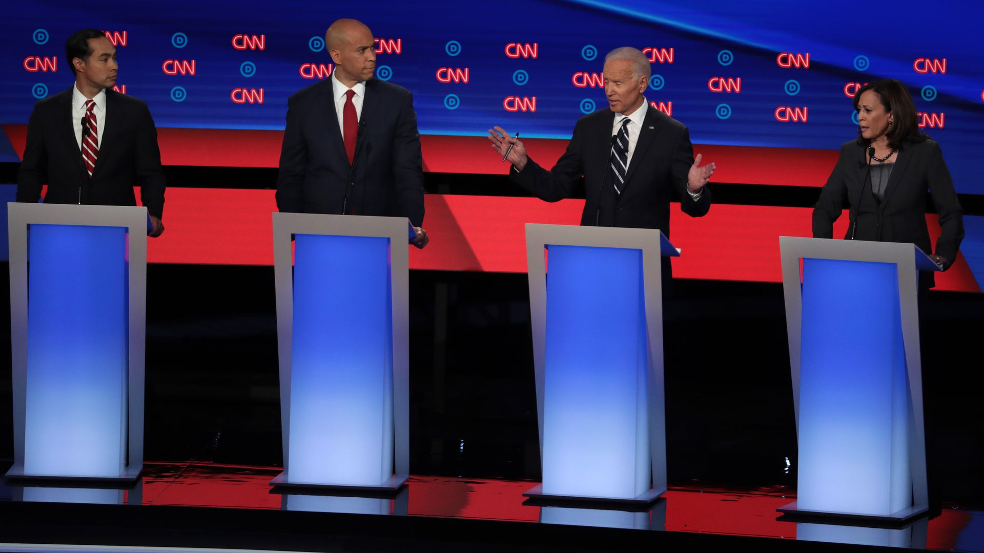 In this image, Castro, Booker, Biden, and Harris stand at podiums on the CNN stage on debate night.