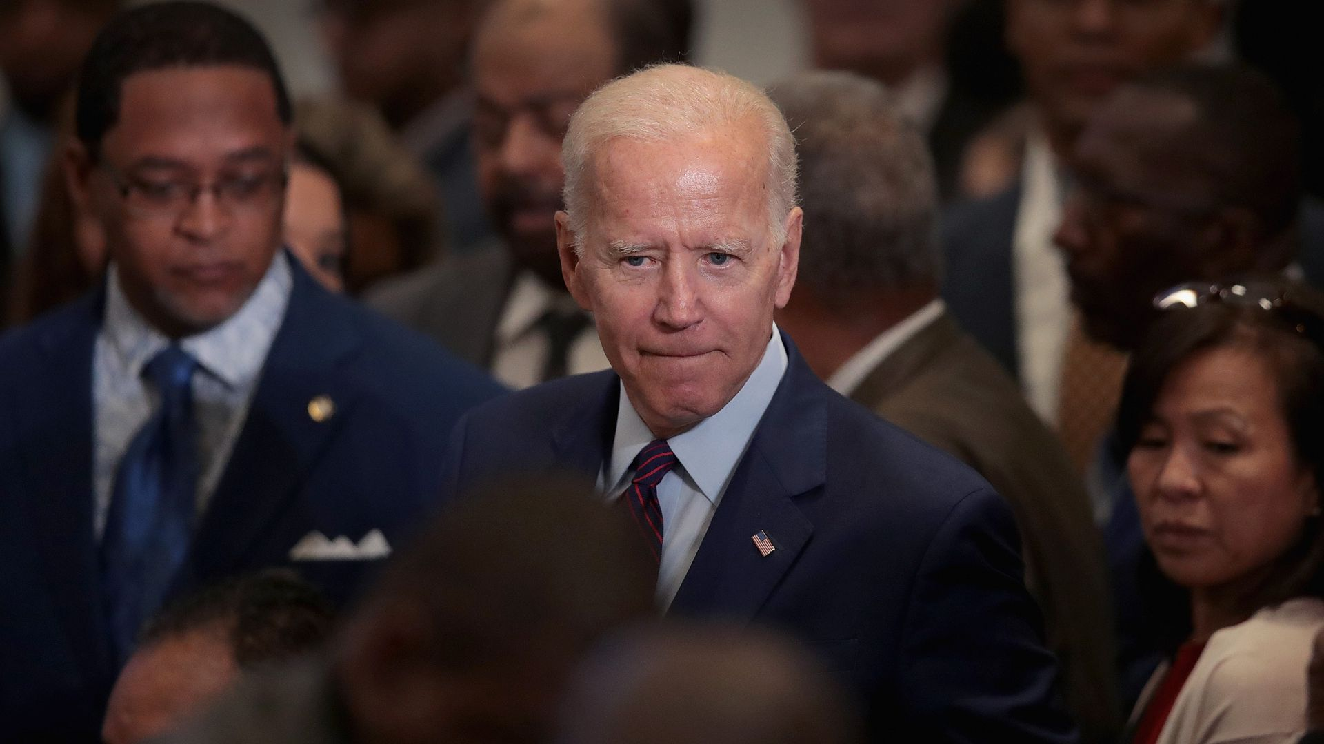 In this image, Biden stands in a crowd.