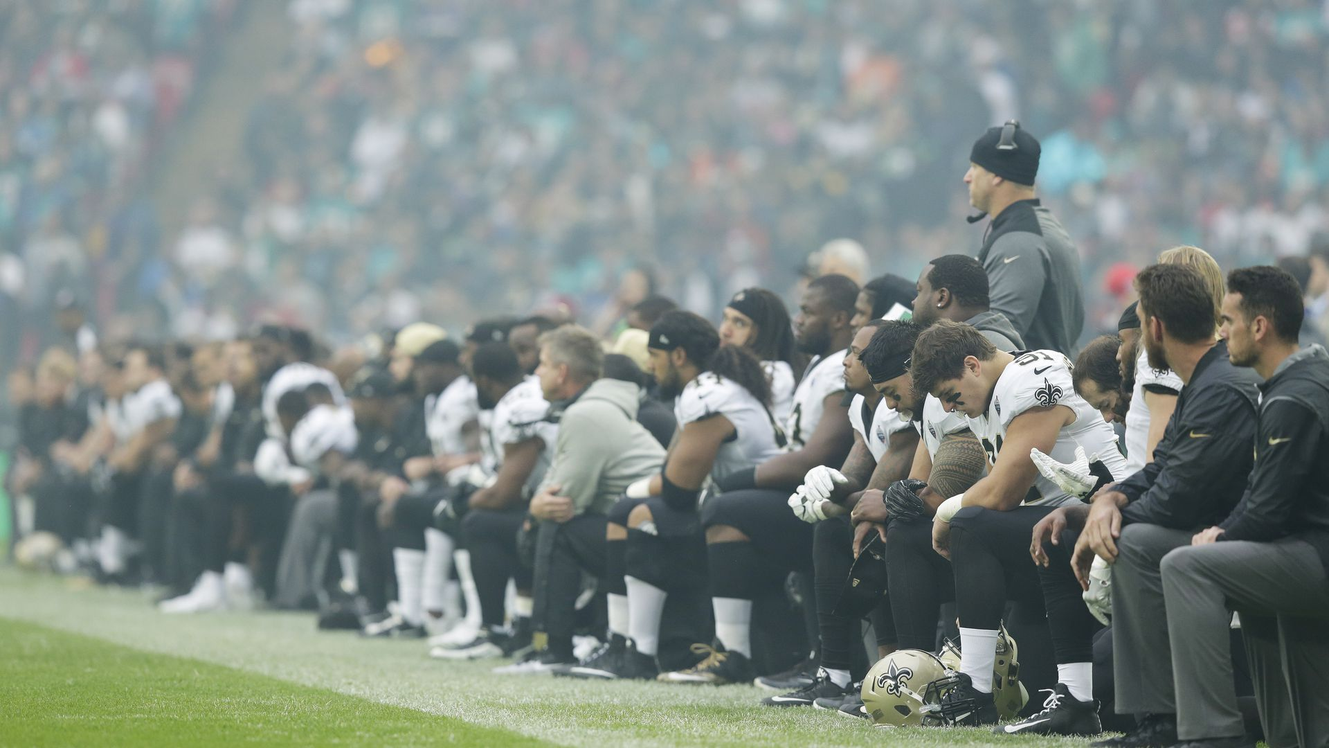 The New Orleans Saints players kneel before the anthem is played.