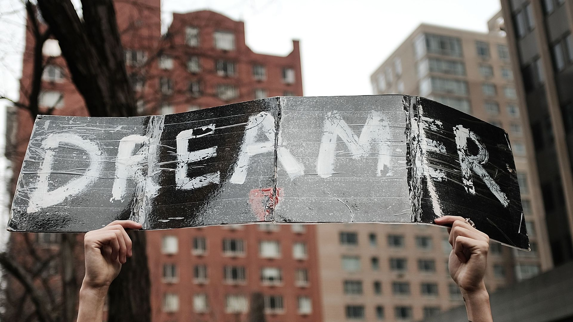 A man holds up a Dreamer sign