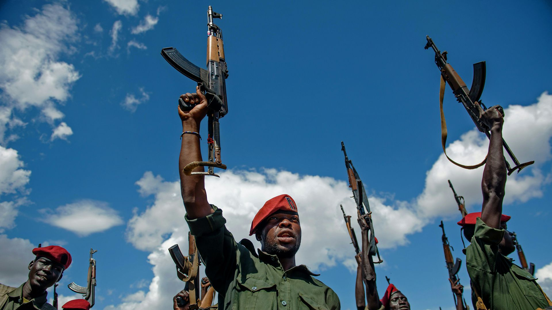 Sudan People's Liberation Army (SPLA) soldiers raise their rifles.