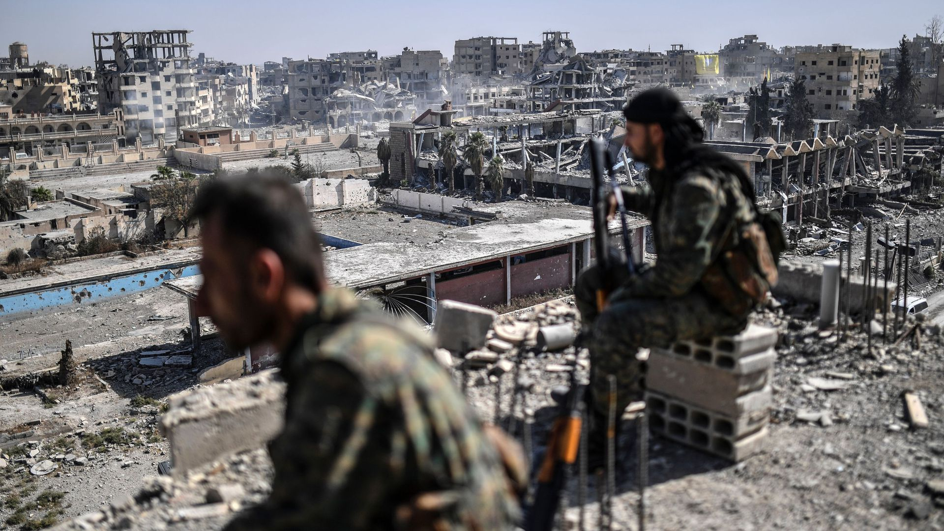 Fighters of the Syrian Democratic Forces (SDF) stand guard on a rooftop in Raqqa.