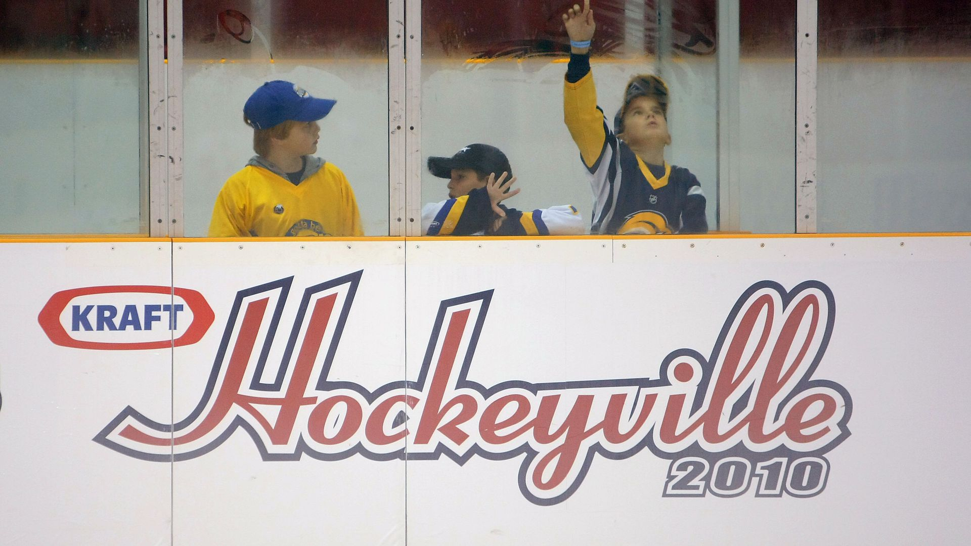 Three children at hockey rink watching through the glass, with a Kraft sign etched into the wall just below them