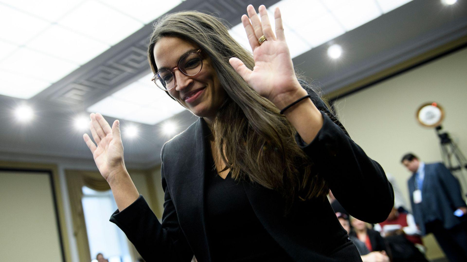 Alexandria ocasio cortez raises her hands.