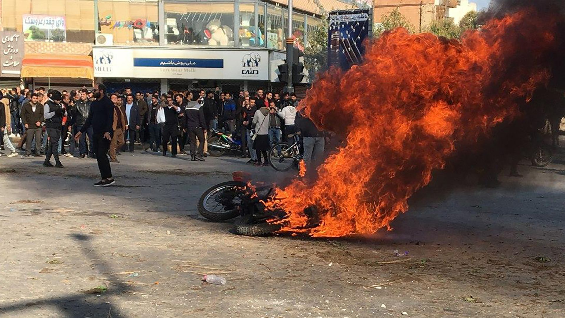 protestors surround a burning motorcycle in a street intersection