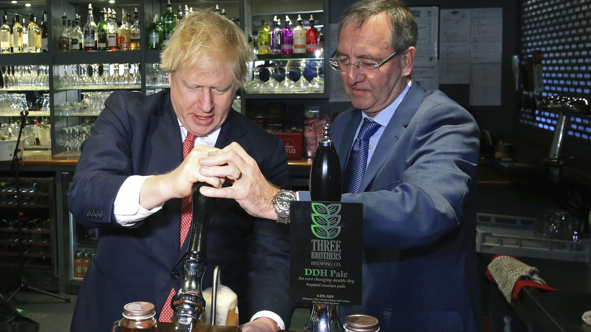 In this image, Boris Johnson stands behind the counter in a bar and pulls down a pint