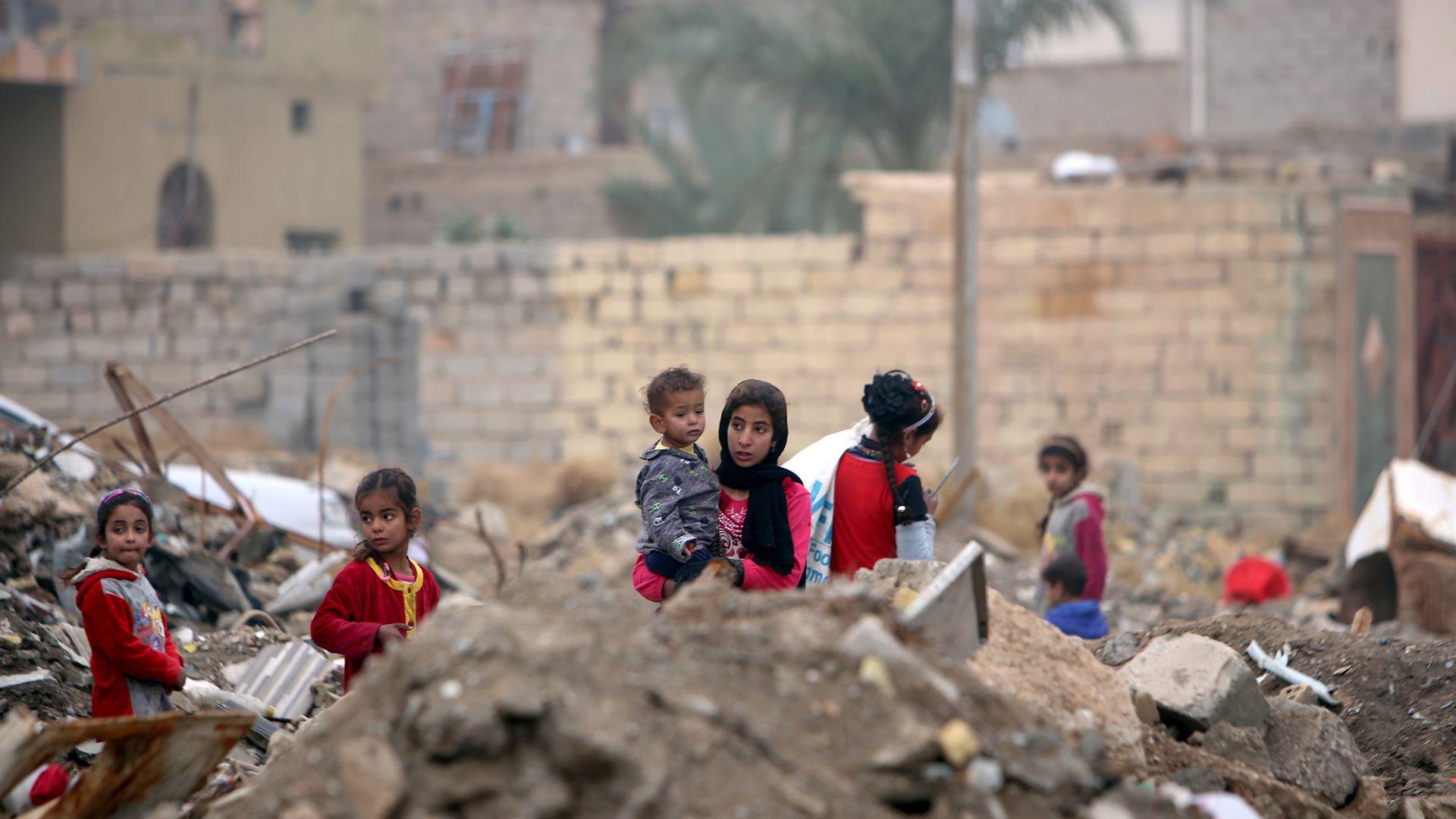 Children stand amid rubble in Fallujah, Iraq.
