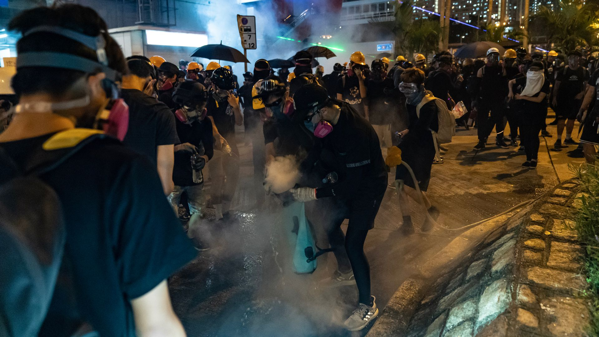 Protesters attempt to put off a tear gas canister during a clash with police in Wong Tai Sin district on August 24, 2019 in Hong Kong