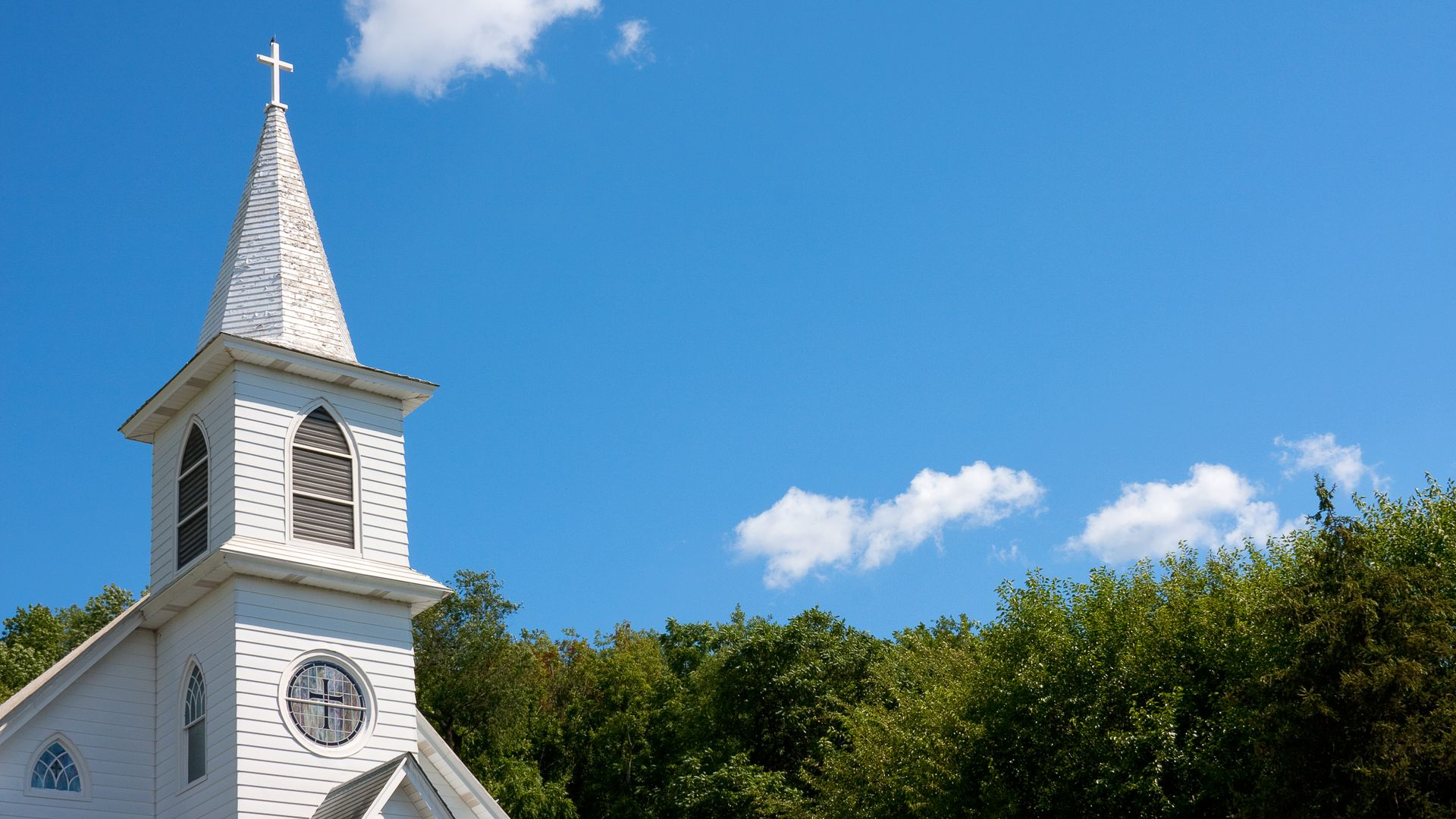 This is an image of a white church against a blue sky.
