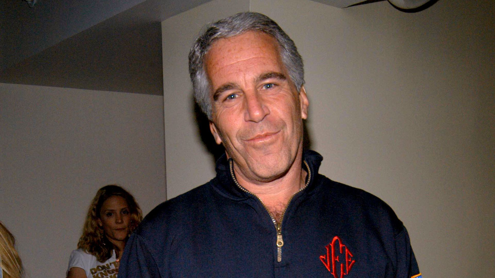 In this image, Epstein stands and looks at the camera while wearing a sweater pullover