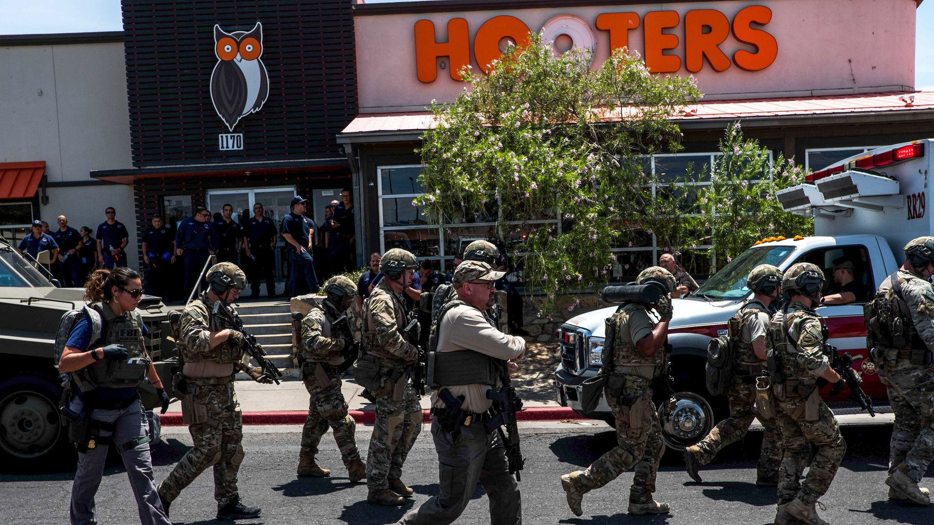 In this image, armed and fatigued officers hold rifles while walking past a Hooter's.