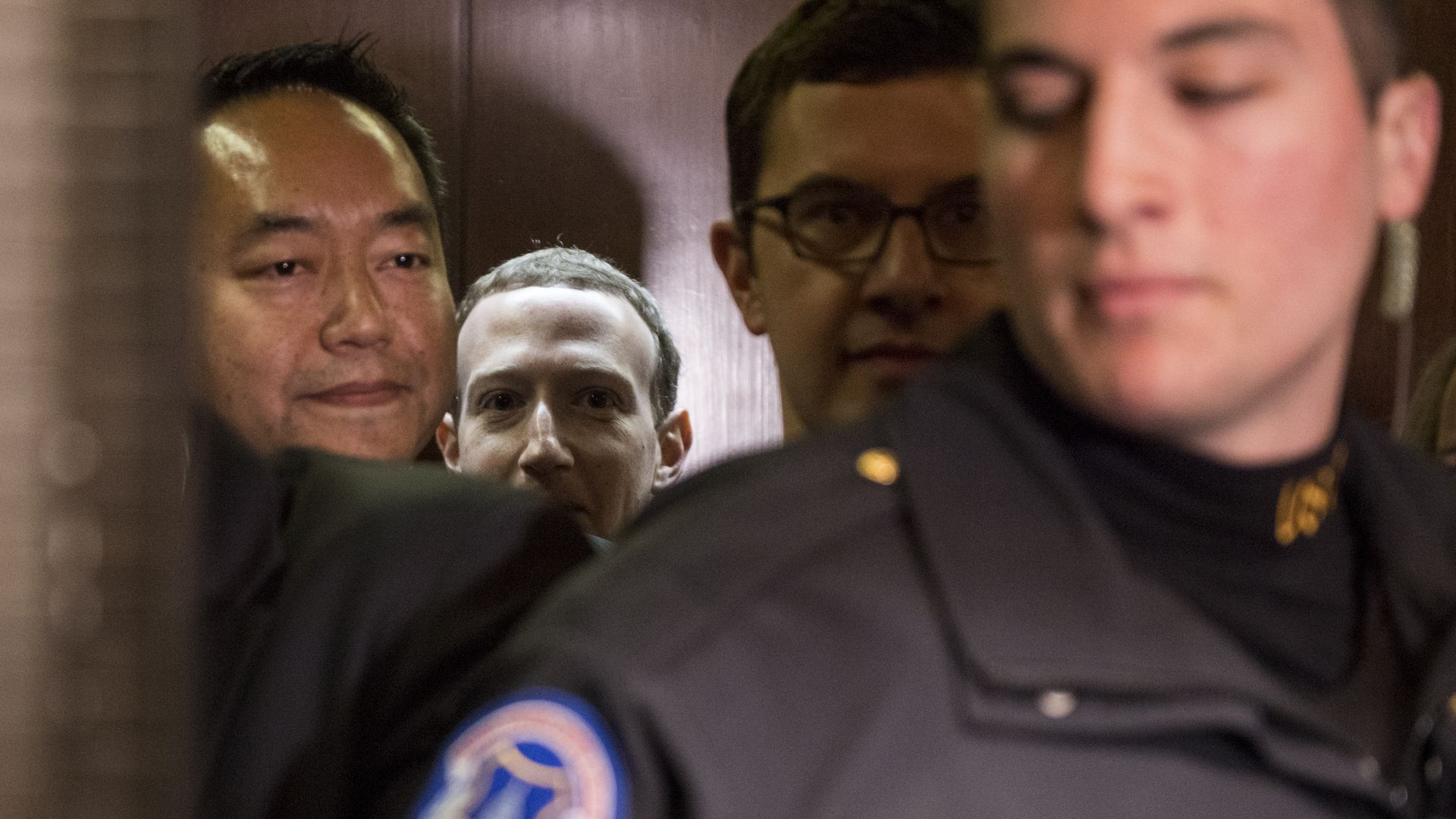 Mark Zuckerberg's face is half visible amid a group of other people