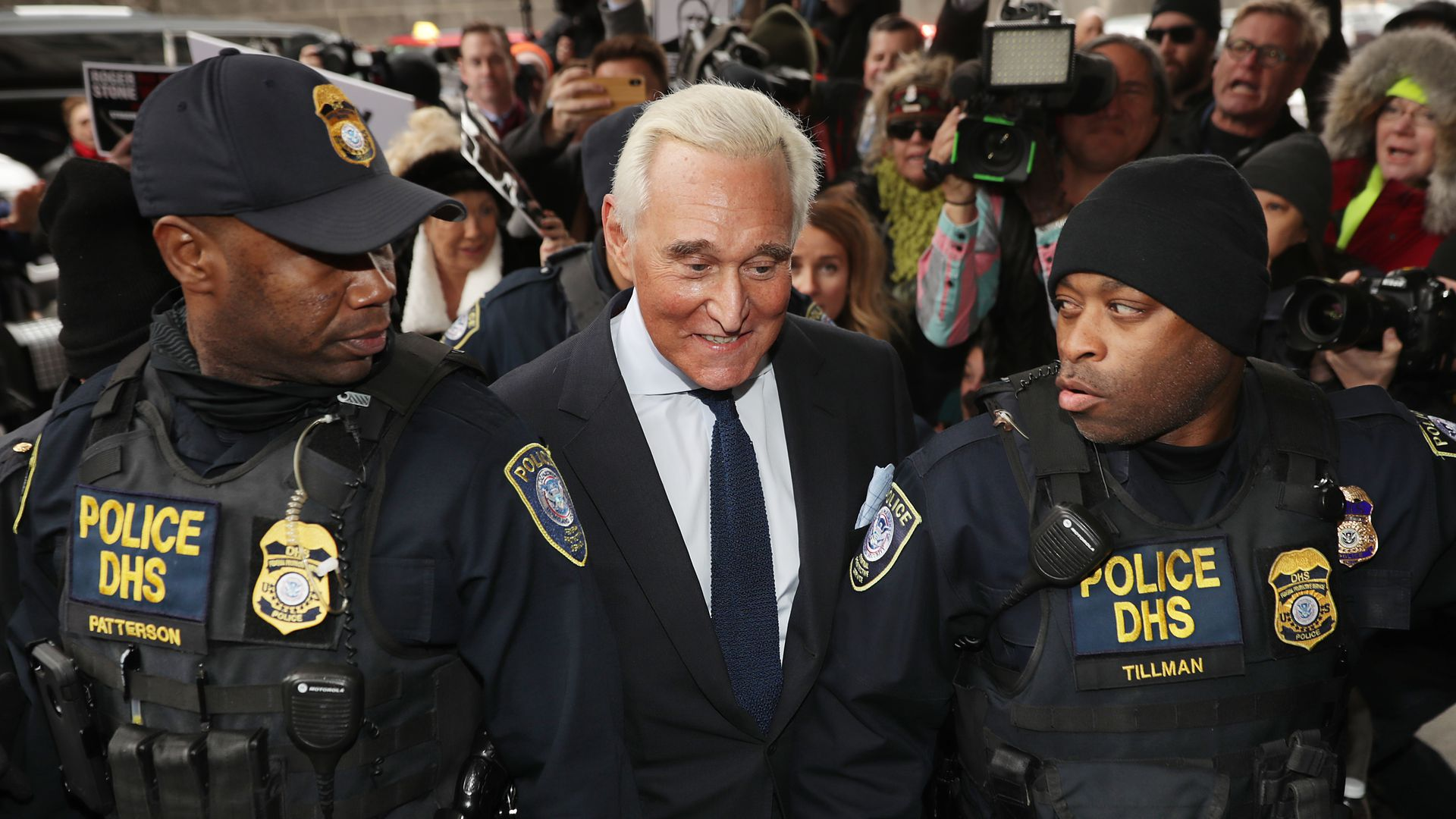 Roger Stone between to law enforcement officers.