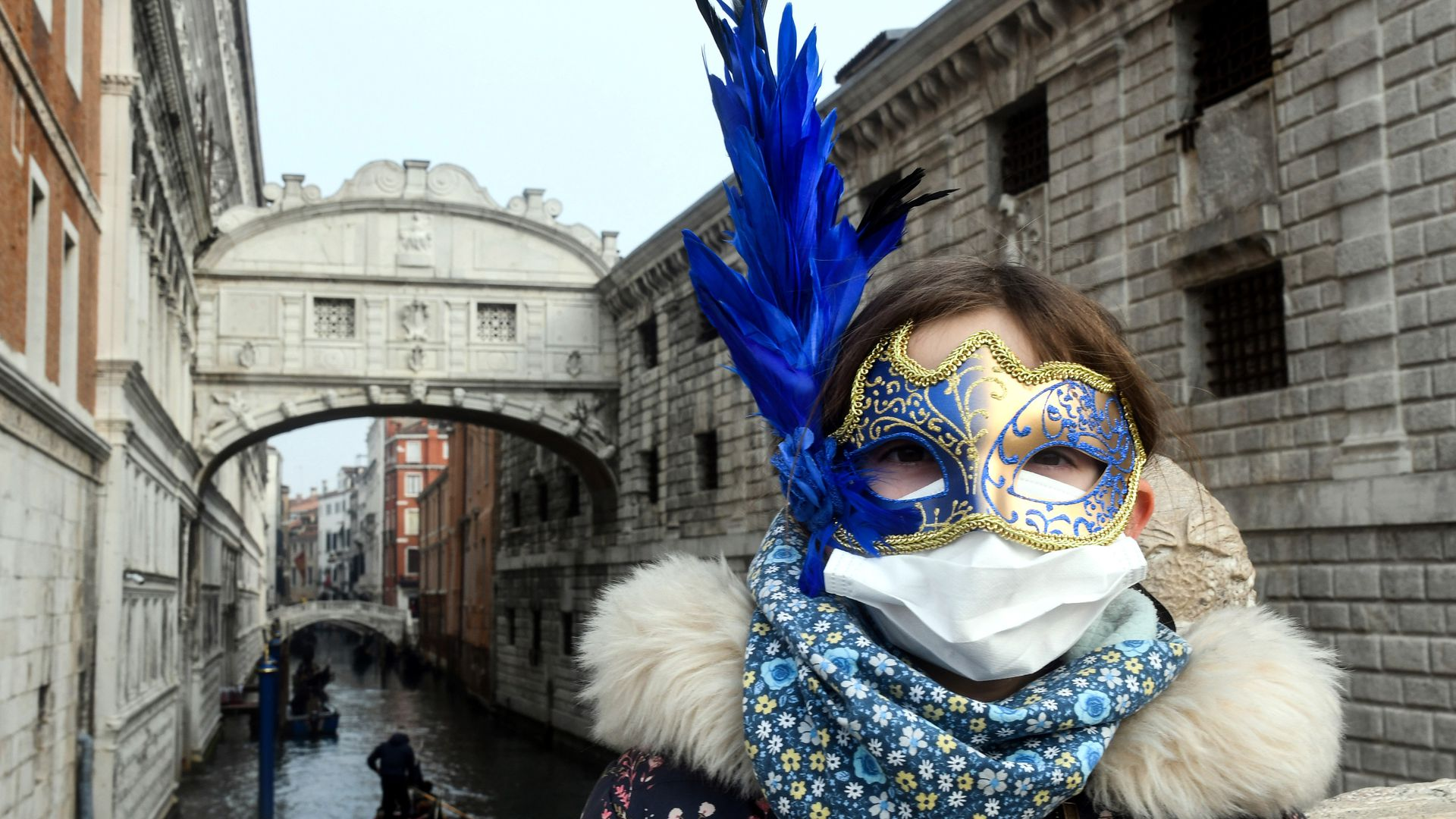 A young tourist wearing a protective facemask and a Carnival mask visits the streets of Venice