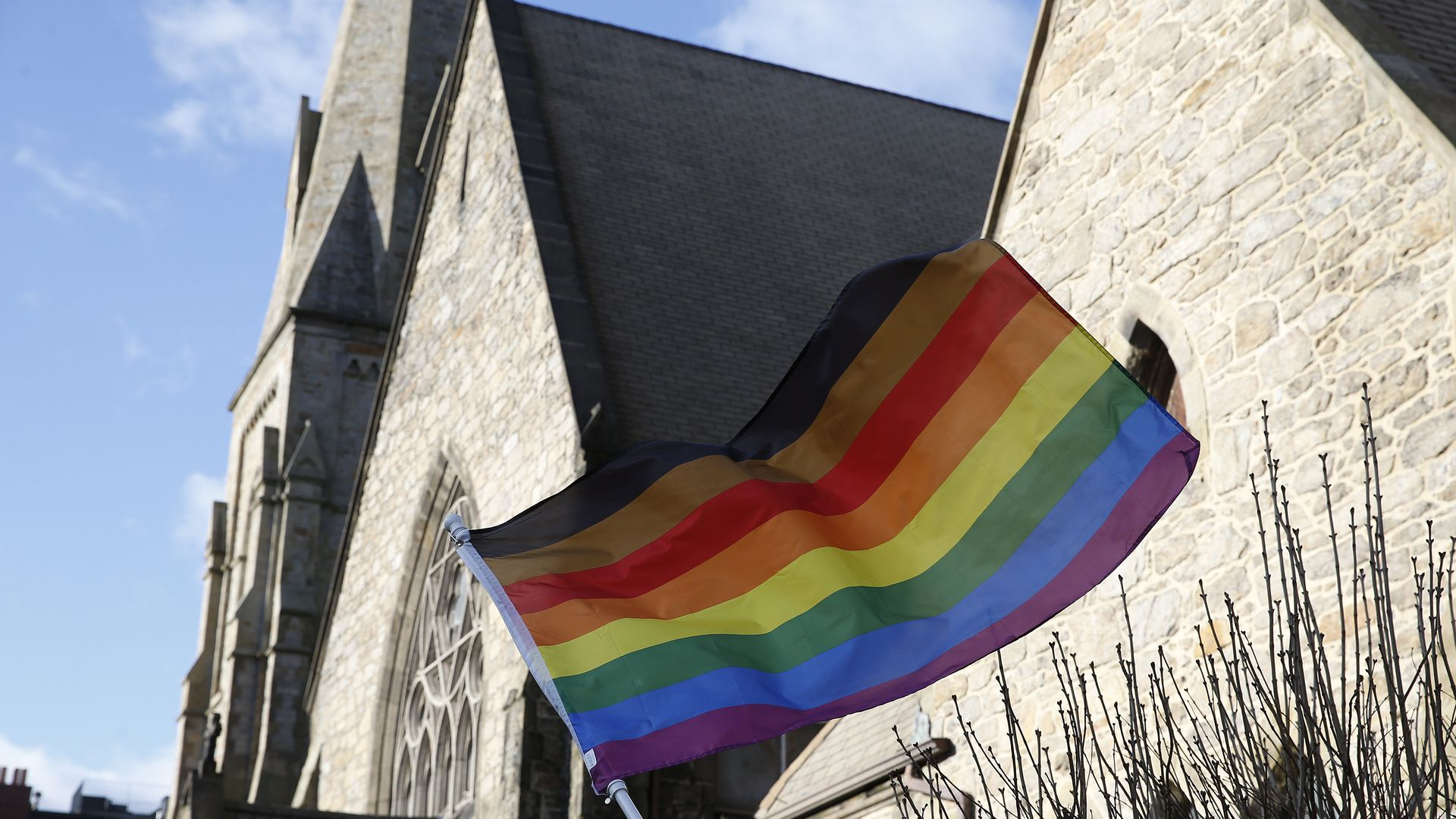 In this image, an LGBTQ pride flag waves in front of a church.
