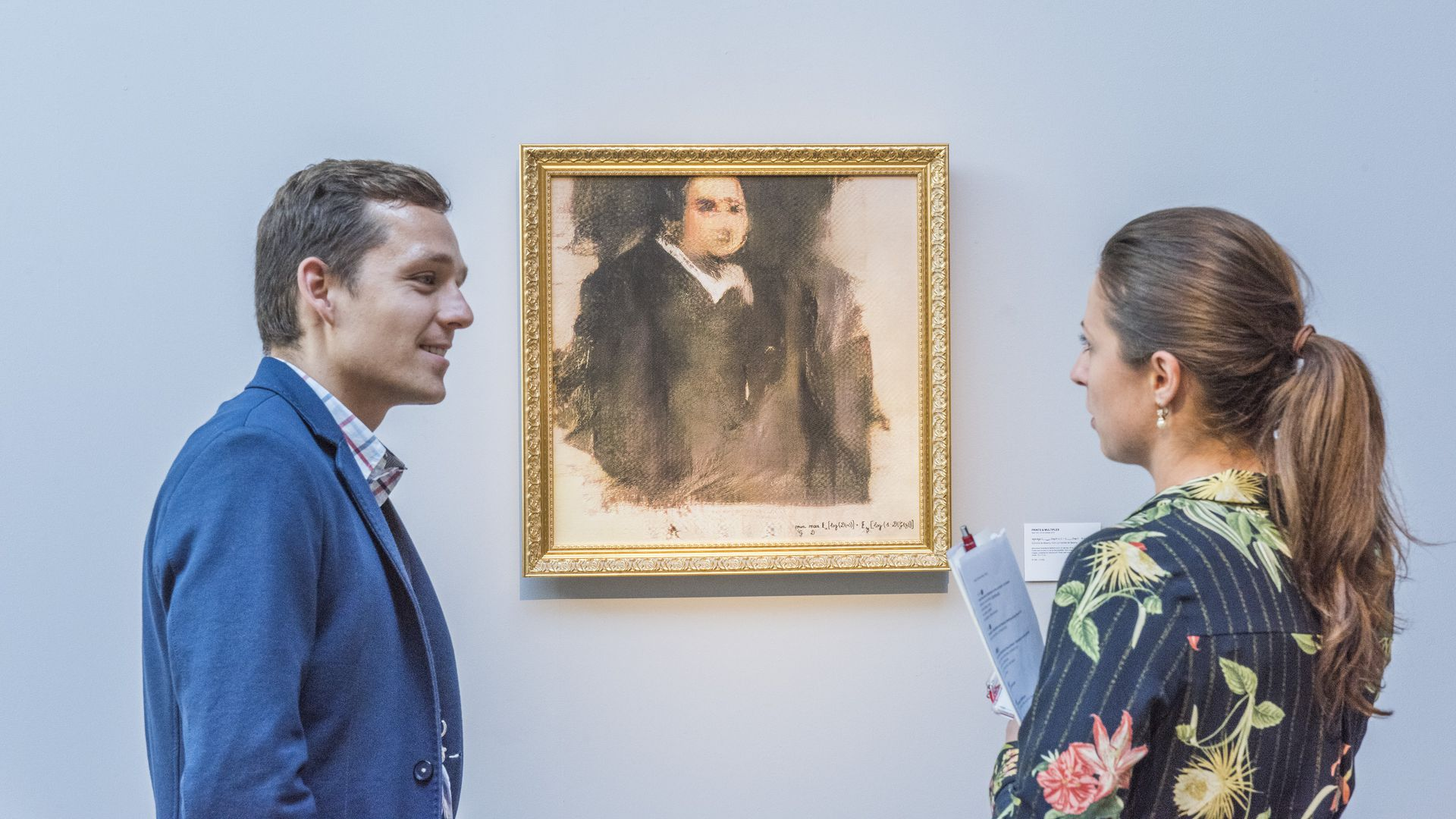 A man and a woman speak to one another in front of an AI-generated portrait in a gallery.
