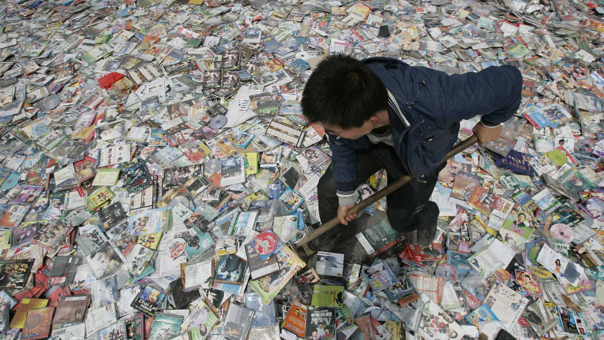 Worker prepares to destroy pirated CDs and DVDs in China