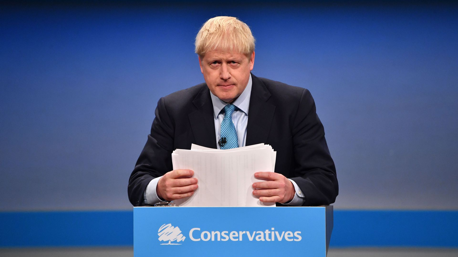 Britain's Prime Minister Boris Johnson shuffles his papers as he delivers his keynote speech