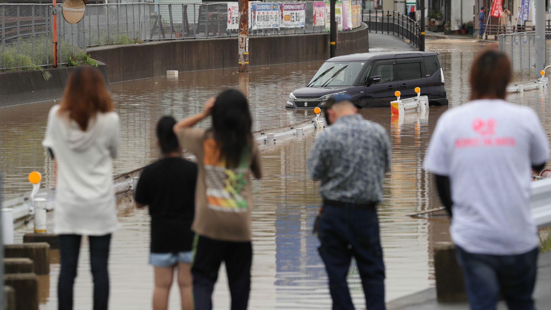 A car sitting on a flooded street.