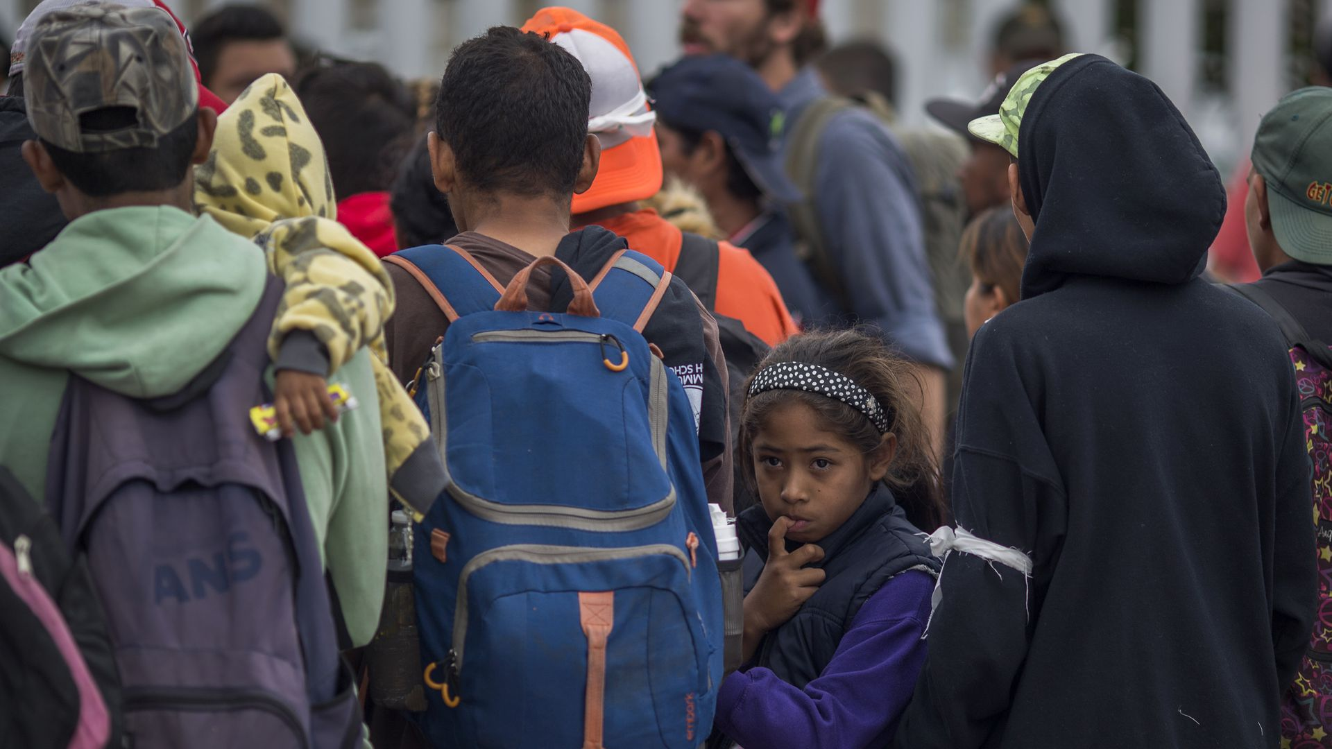 Members of Central American caravan. One young girl looks back with her finger in her mouth