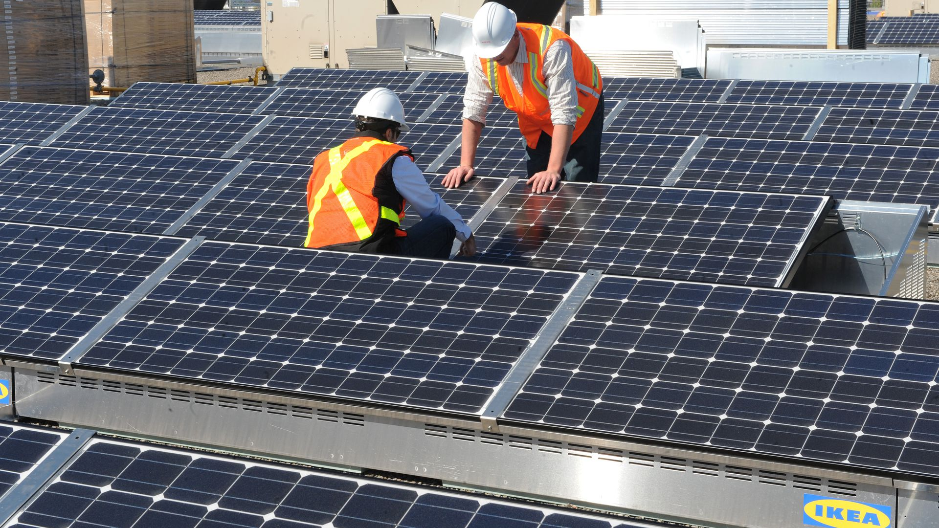 Workers install solar panels on the roof of an Ikea