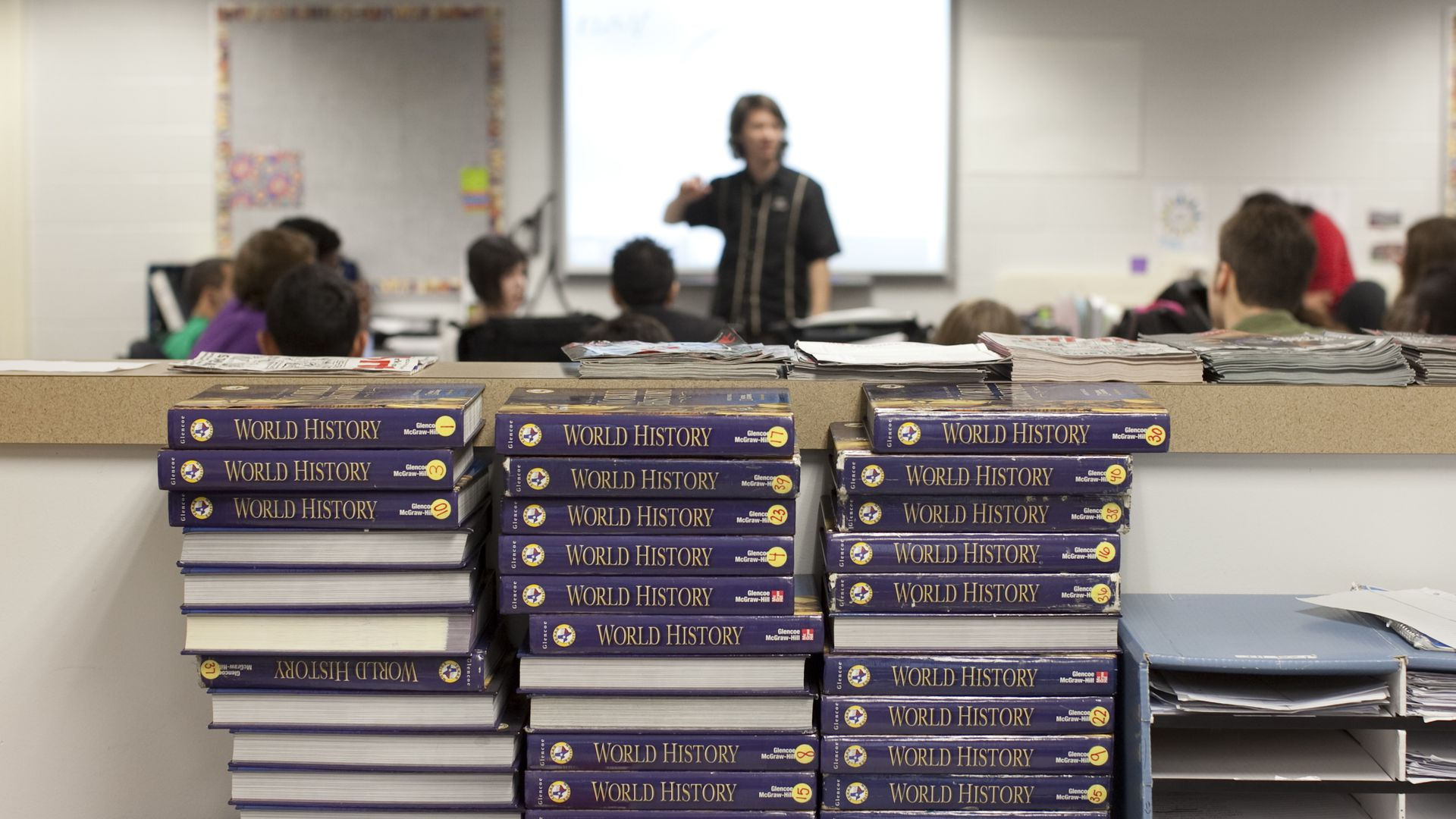 World history textbooks stacked up on a table.