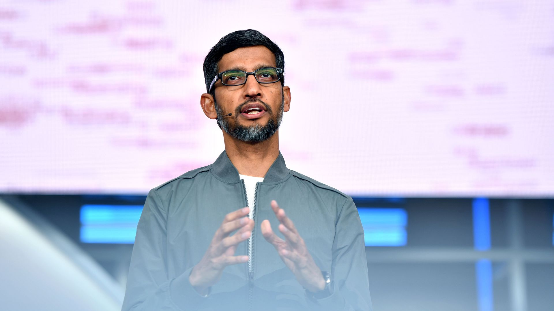 In this image, Sundar Pichai stands on stage and speaks to an audience while wearing a microphone and glasses