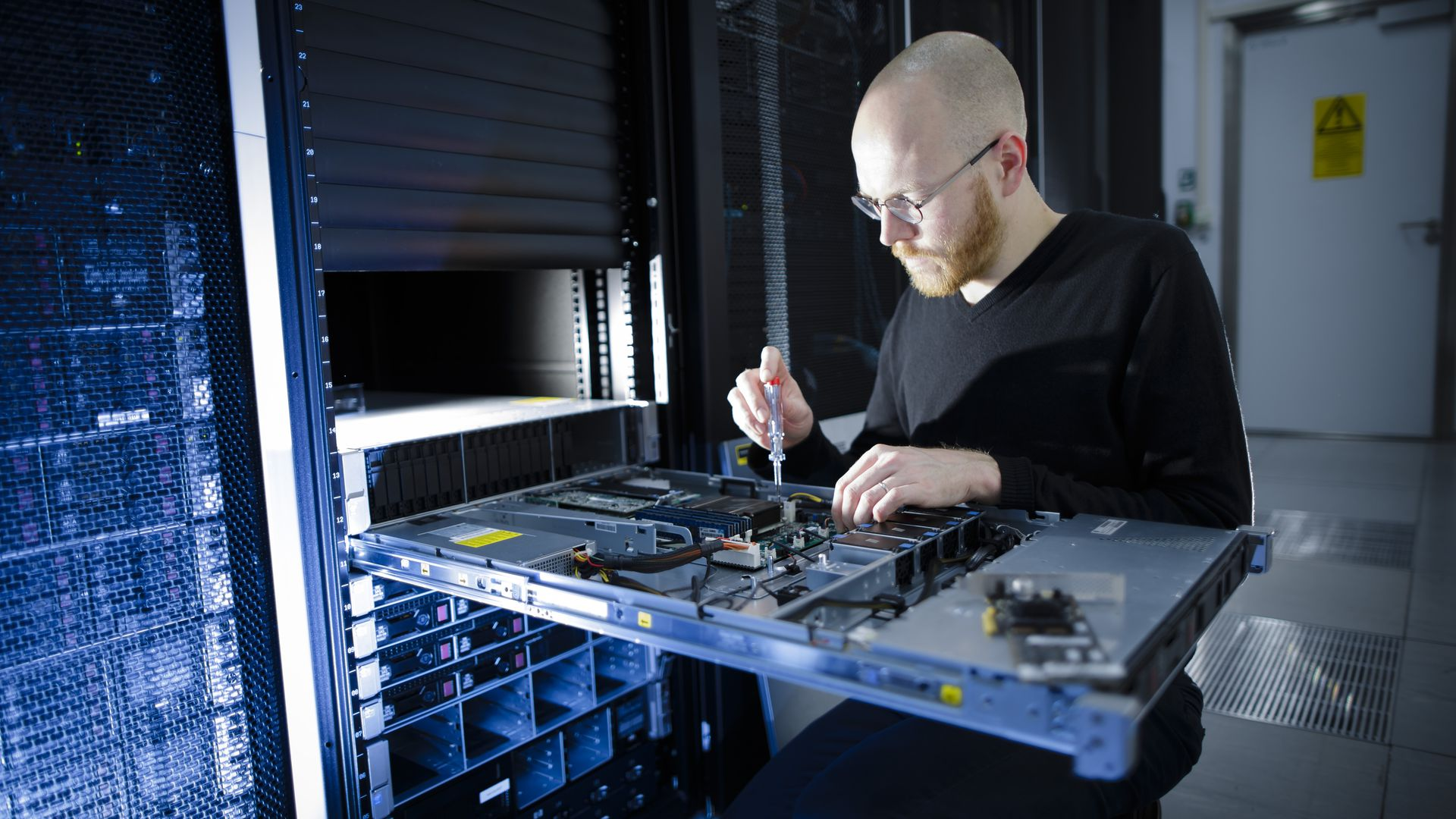 A man unscrews a server part in a data center.