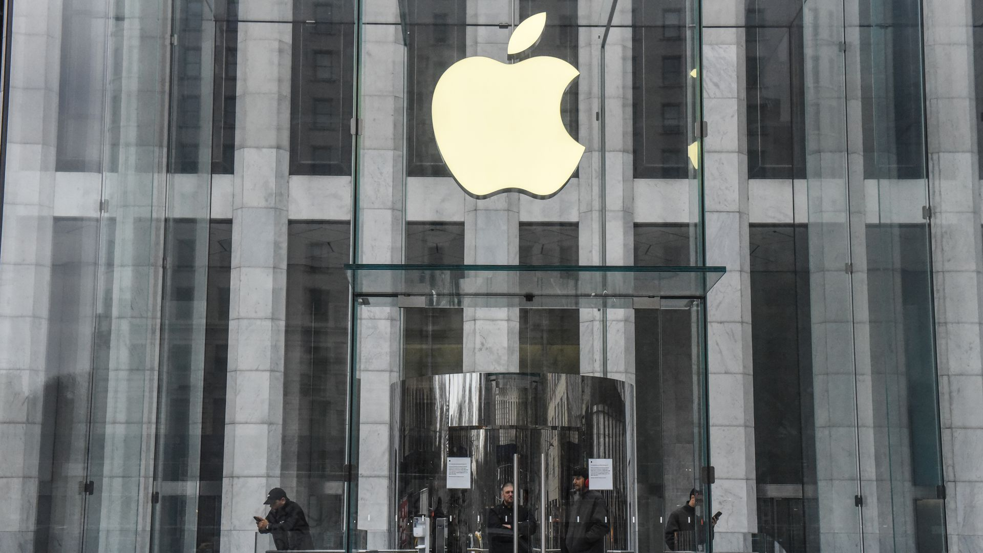 People standing at the entrance of Apple's flagship store in New York City.