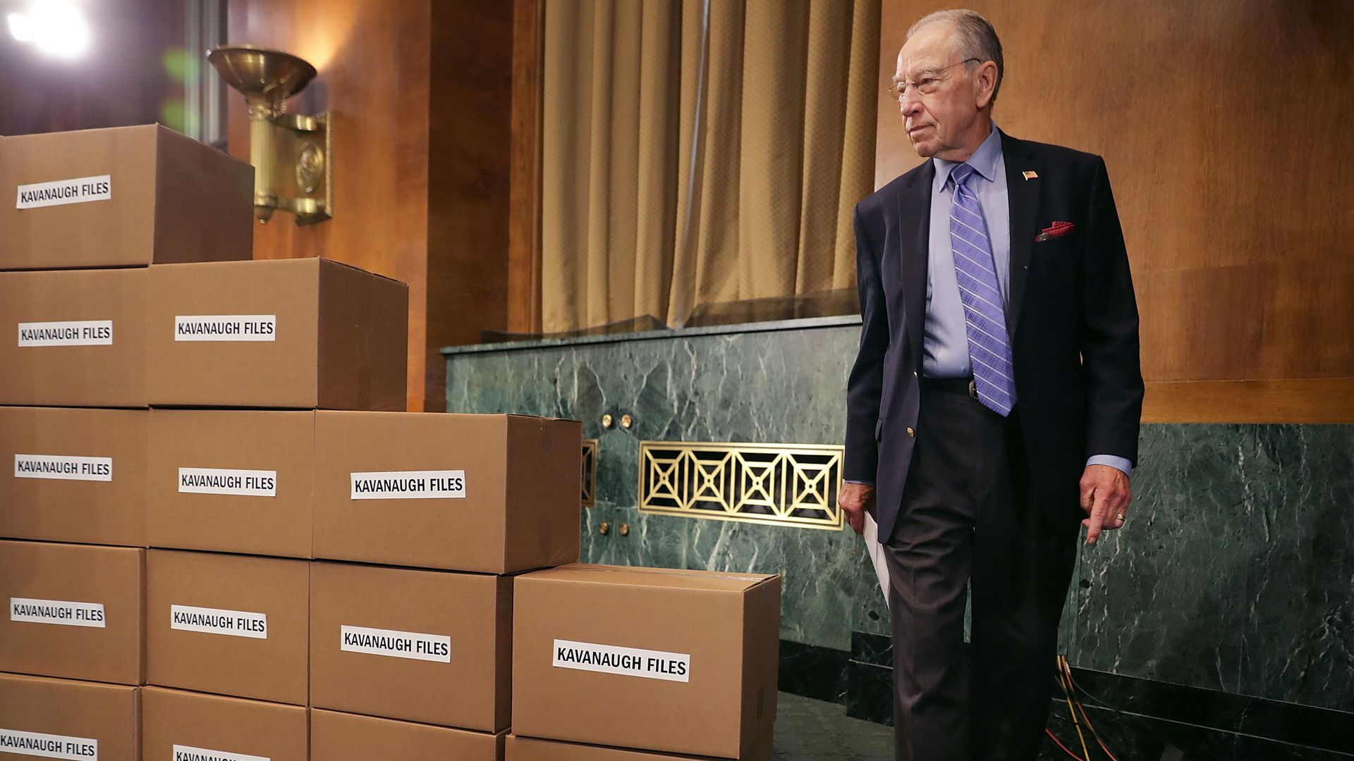 "Chuck Grassley walking to the front of a pile of cardboard boxes labelled ""Kavanaugh Files"""