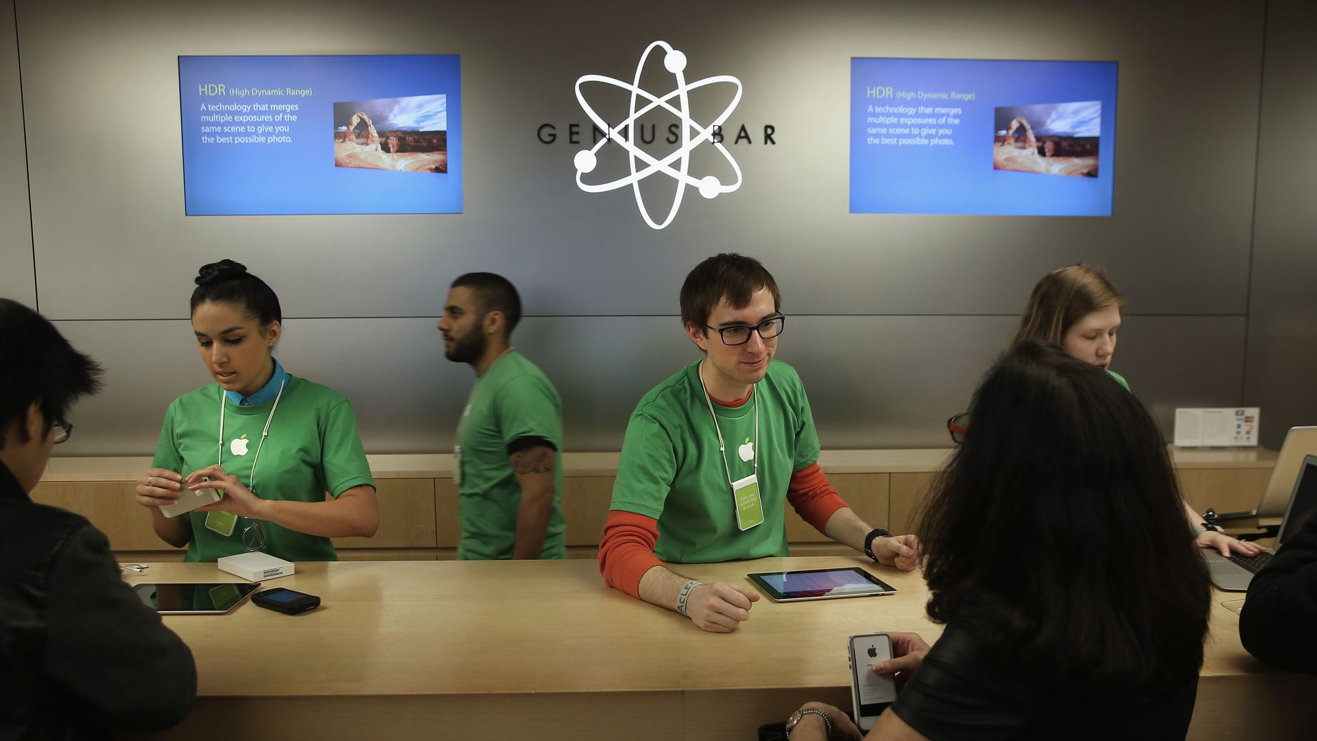 "A man in a green shirt, layered over a red long-sleeved shirt, leans over a counter in front of a sign that says ""Genius Bar"""