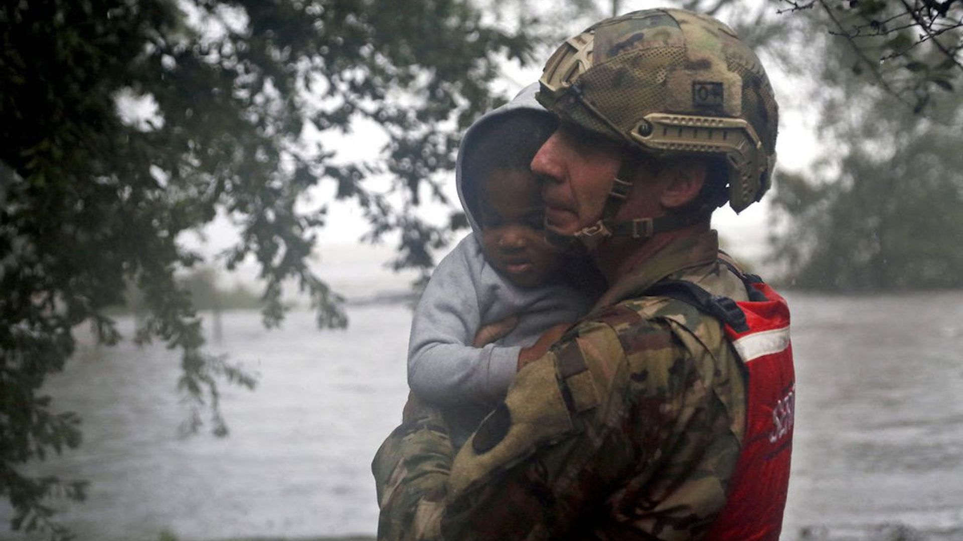 A National Guard member carries a child.