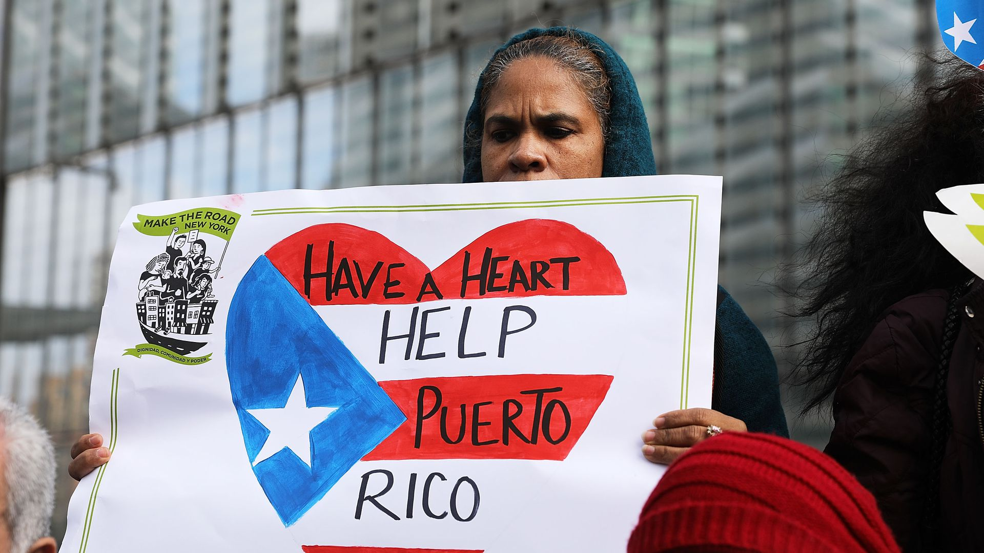 "Woman holding a sign with an american flag heart which says ""have a heart help puerto rico"""