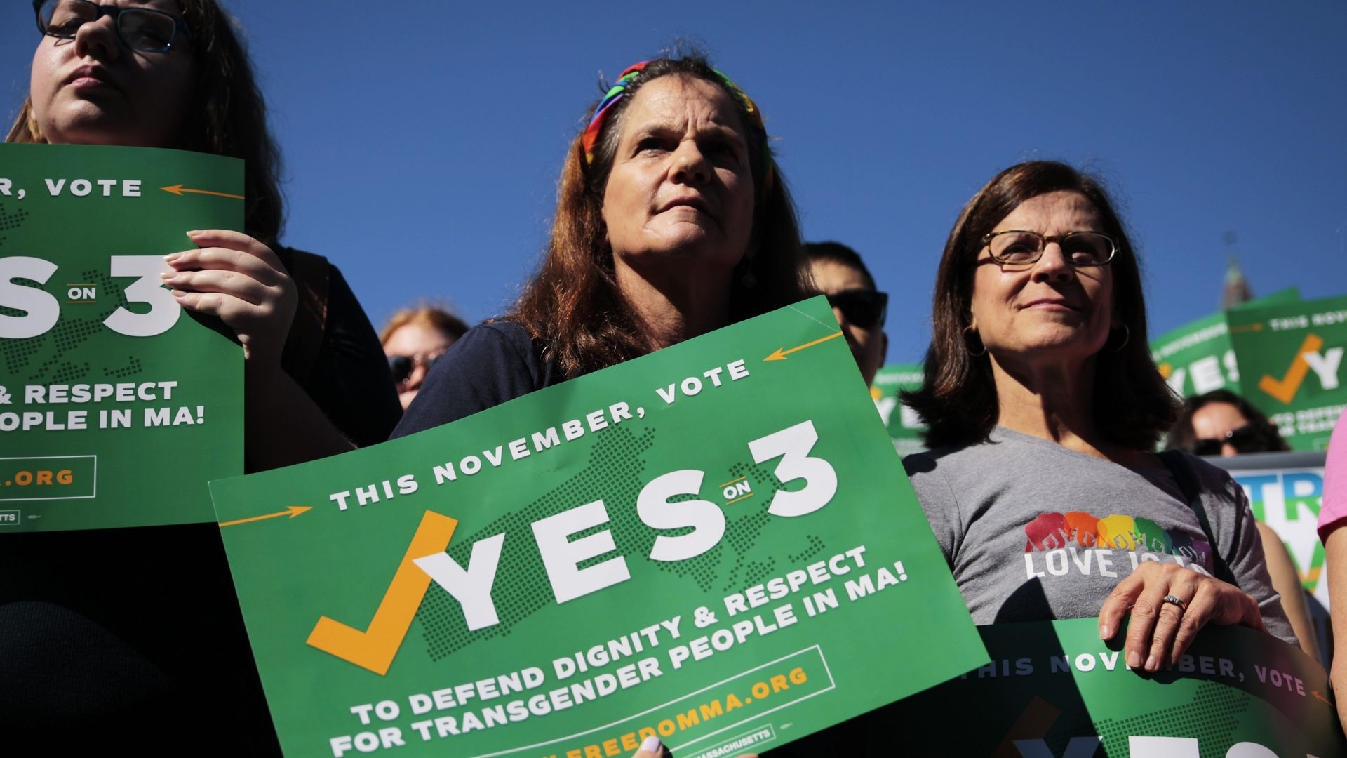 "Women hold up signs that say ""Yes on 3"""