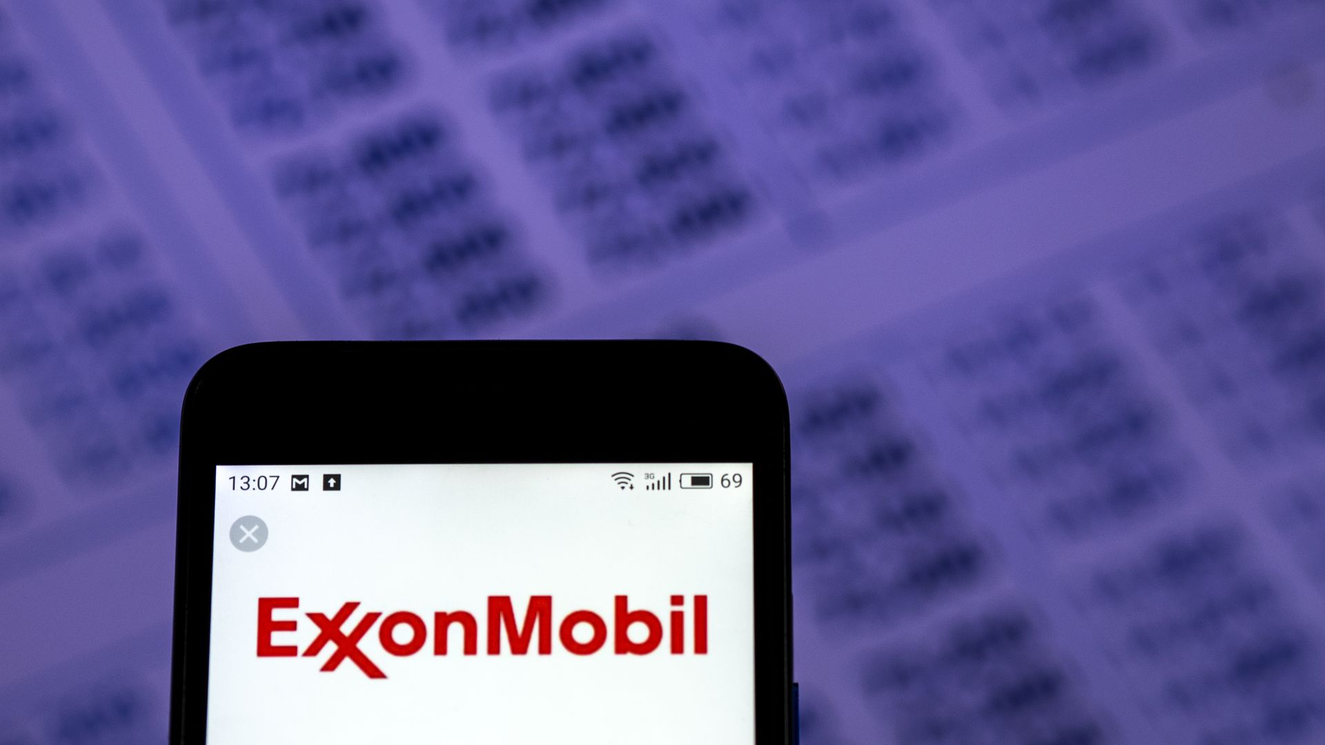 In this image, a phone displaying the ExxonMobil logo is displayed in front of a purple background with numbers.