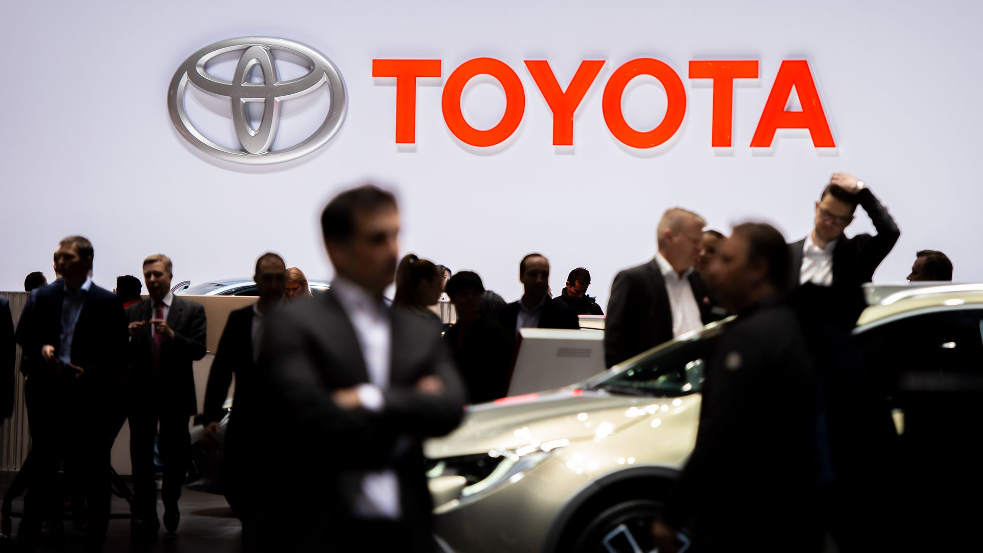 In this image, crowds of mostly suited people walk around a show floor with the Toyota logo overhead.