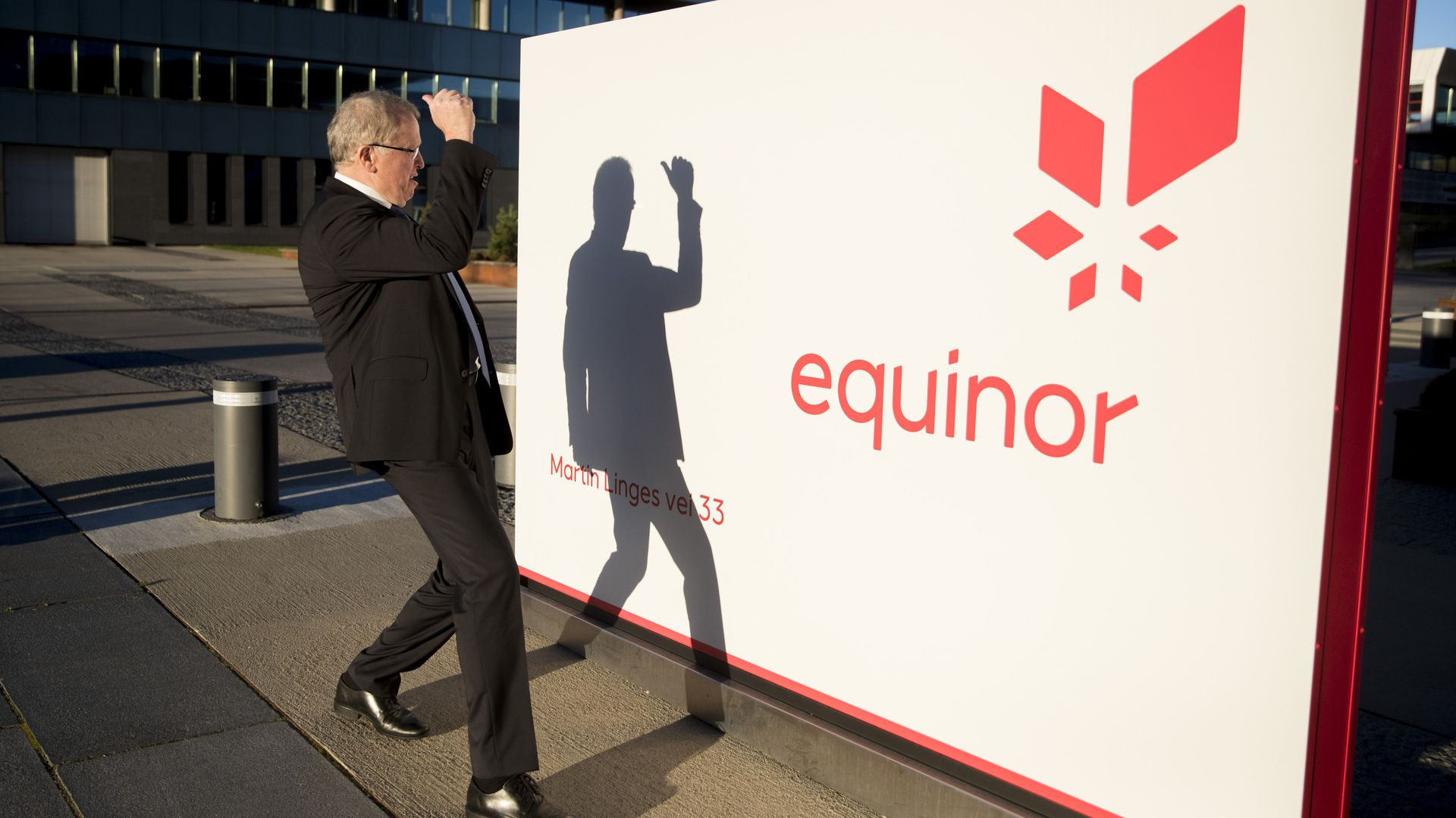 In this image, a suited man shields his face from the sun and looks at his own shadow reflected on a billboard with the Equinor logo on it.