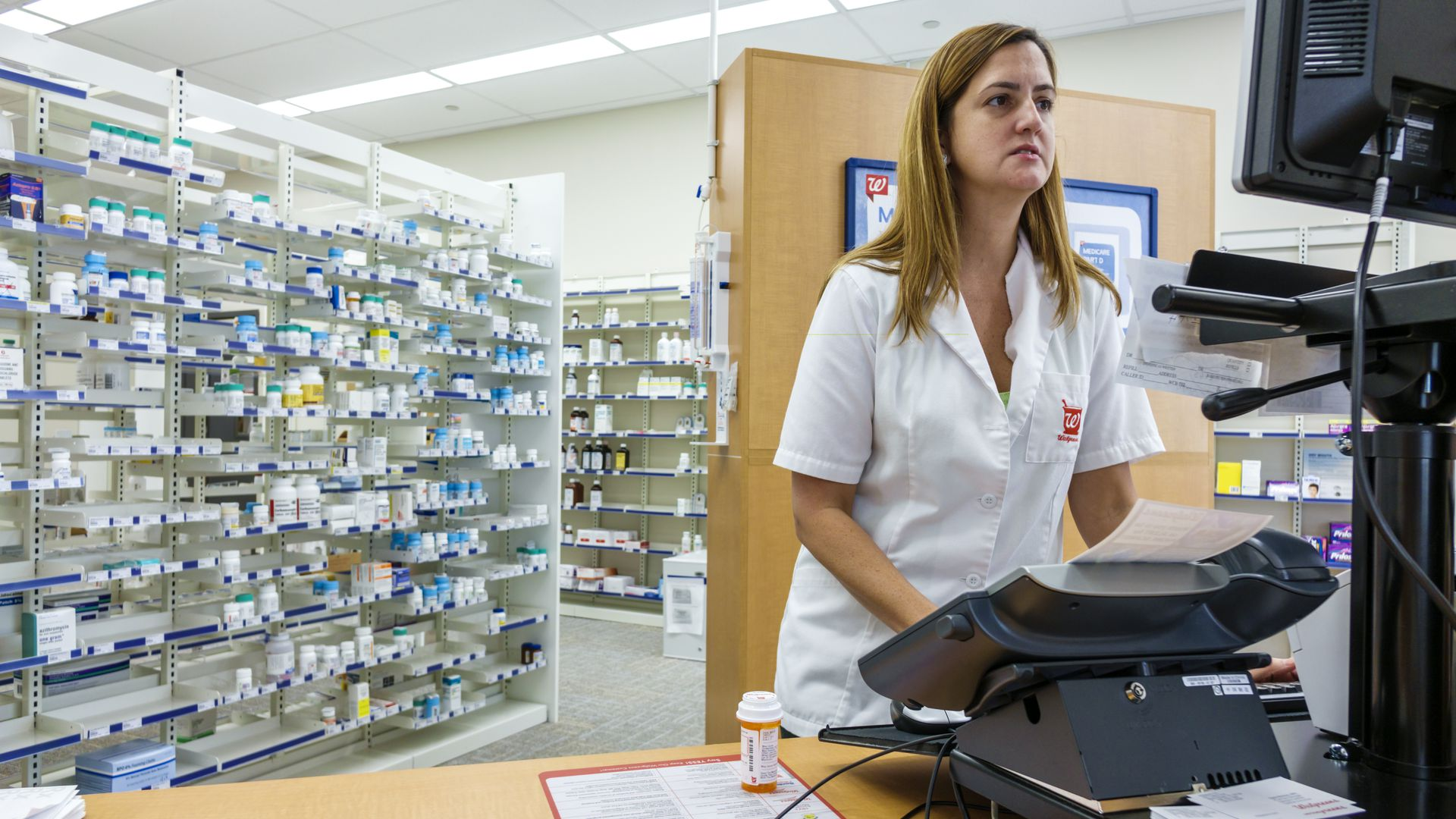 A Walgreens pharmacist fills an order.