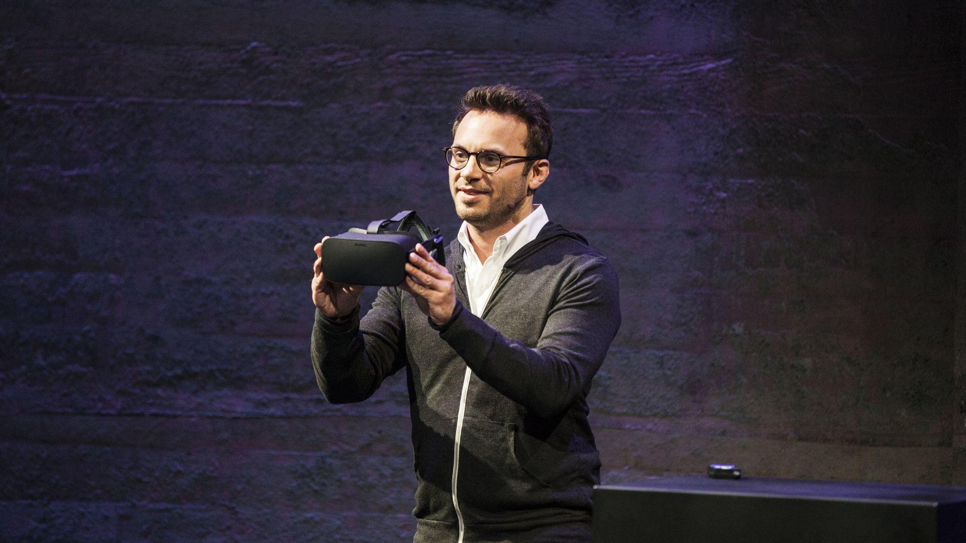 Photo of Oculus co-founder Brendan Iribe holding a virtual reality headset.