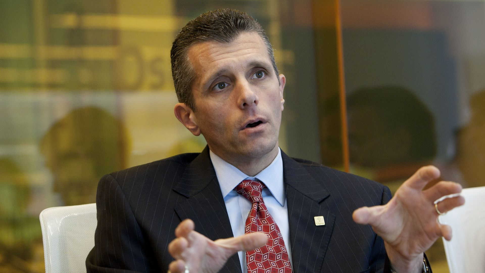 Cigna CEO David Cordani talks in a board room.