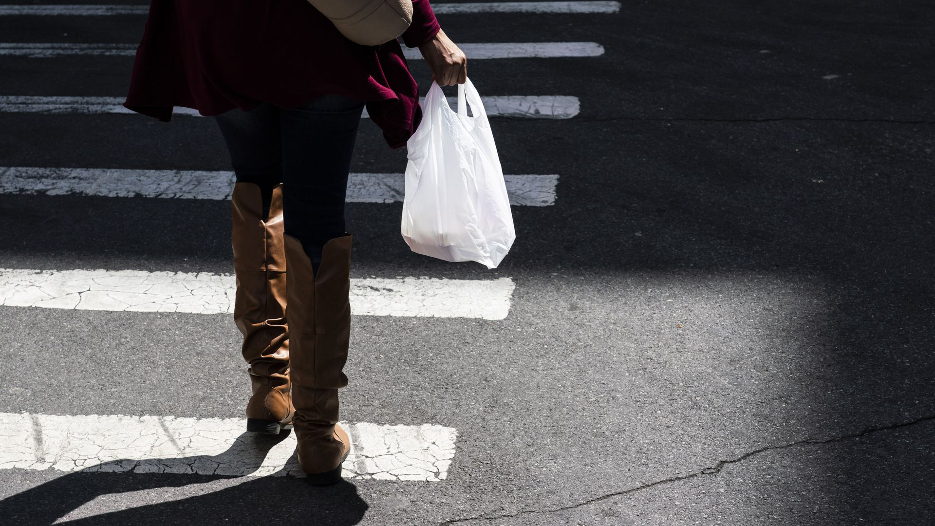A photo of a person's legs walking along a crosswalk with a plastic shopping bag in their right hand