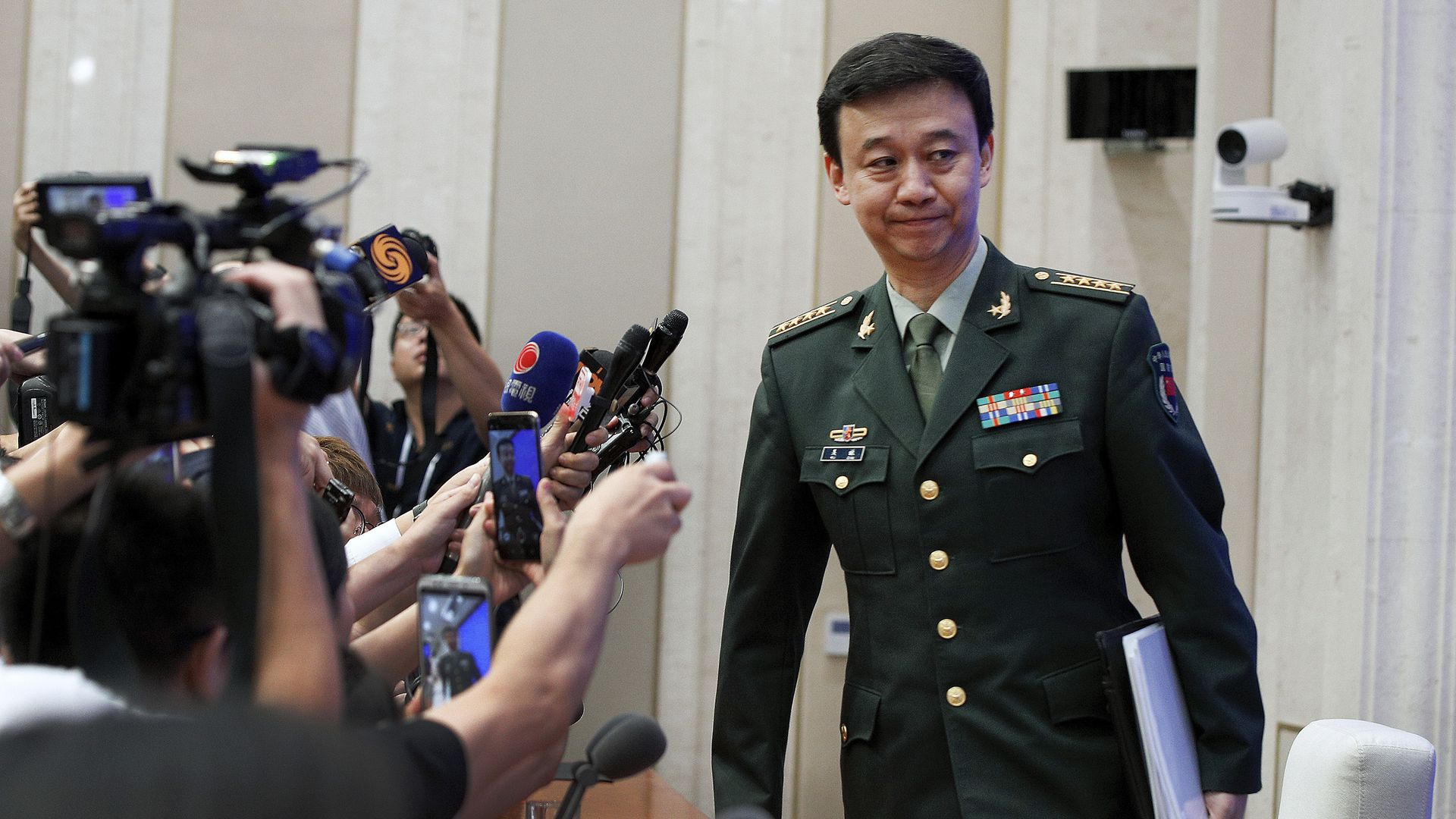 China's Defense Ministry spokesman Wu Qian leaves as journalists are asking question at a press conference at the State Council Information Office in Beijing, Wednesday, July 24.