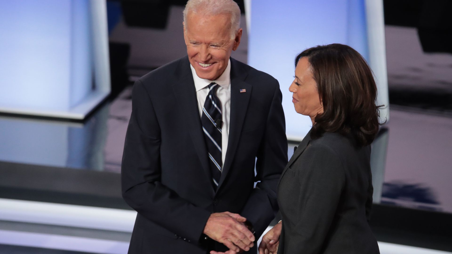 In this image, Biden and Harris shake hands and smile.