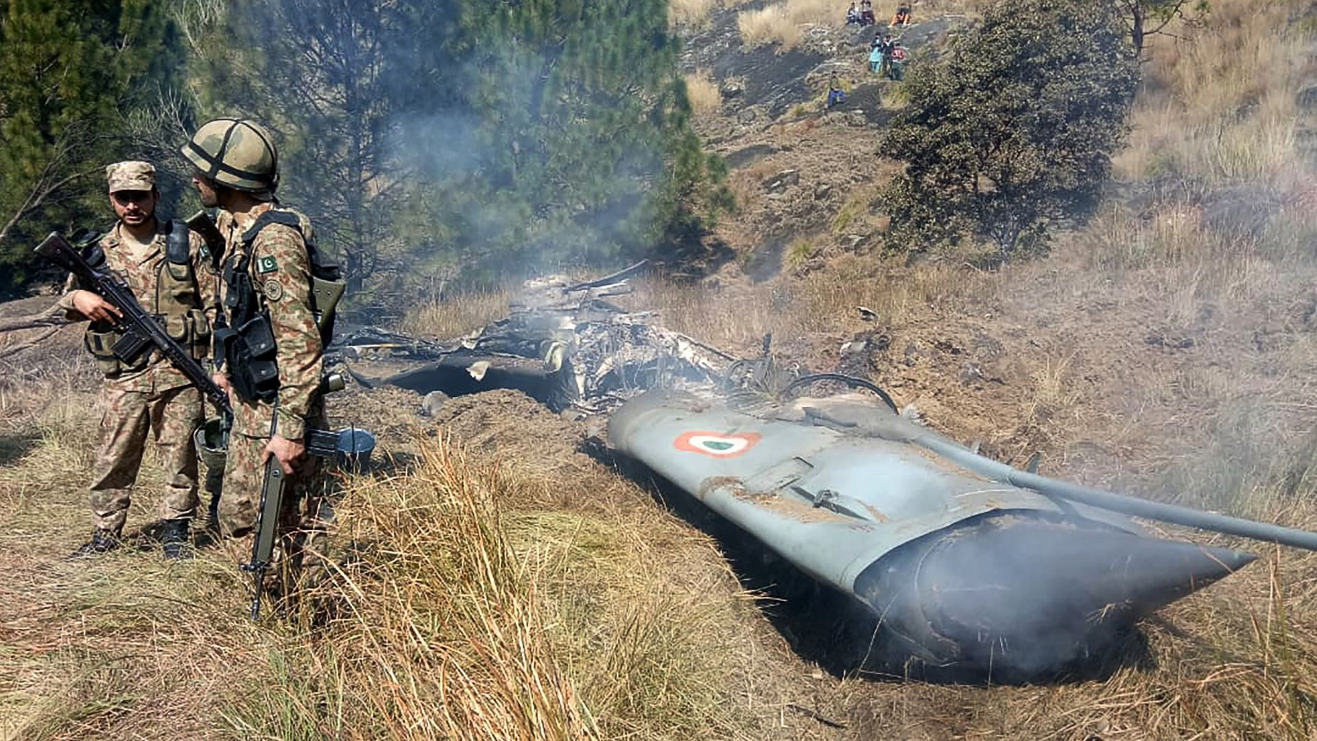 Pakistani soldiers stand next to what Pakistan says is the wreckage of an Indian fighter jet shot down in Pakistan controled Kashmir at Somani area in Bhimbar district
