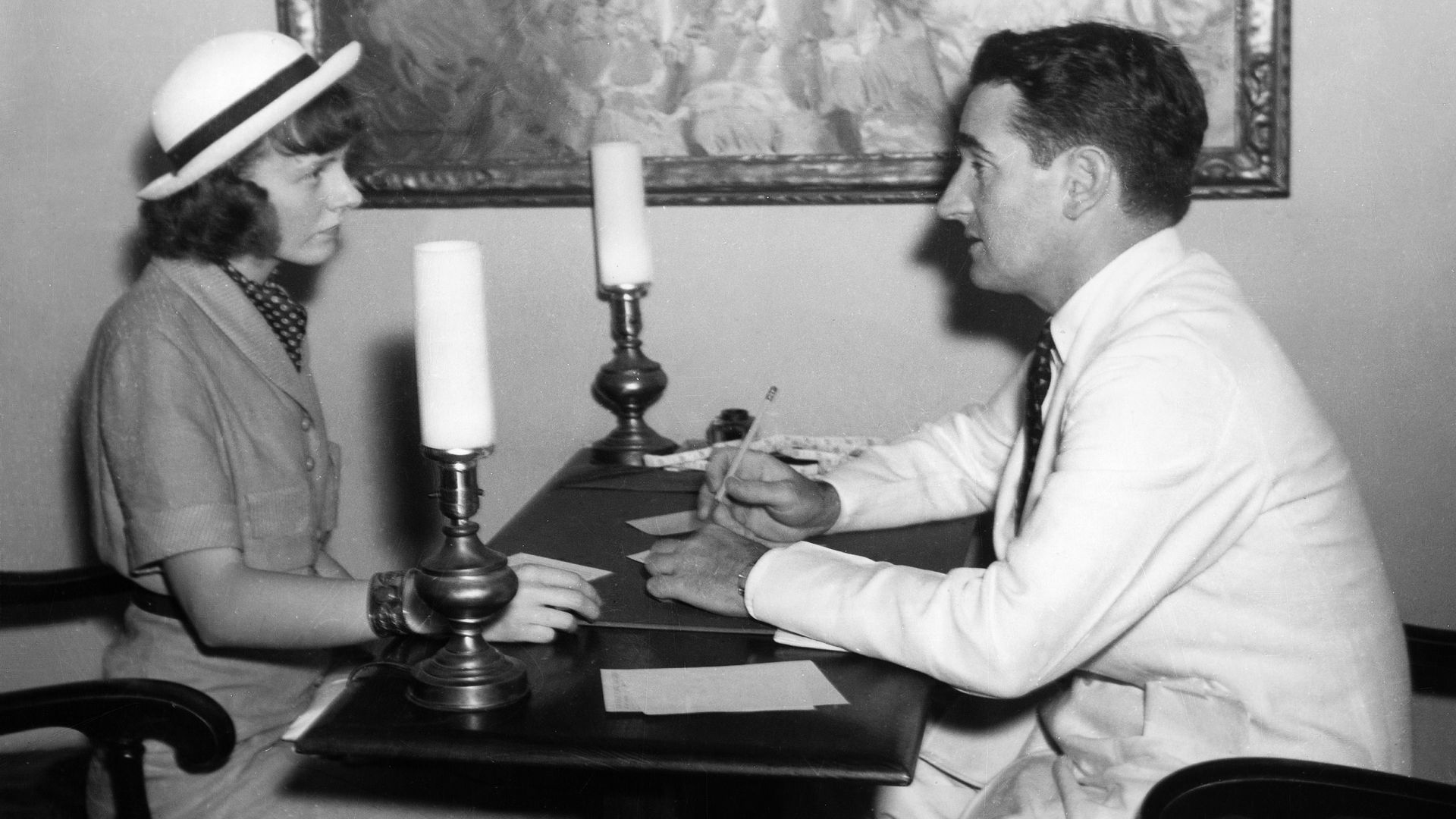 A black and white photo of a man and a woman conversing across a table